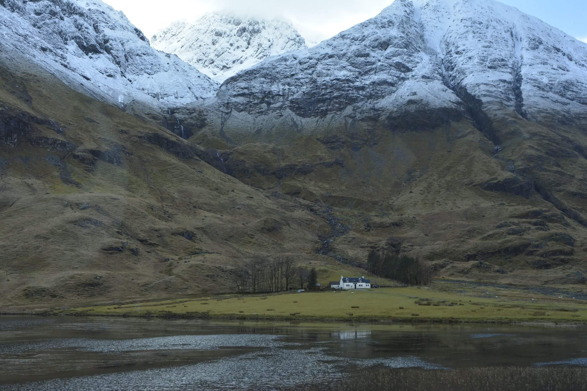 Scotland's mountains and valleys, with a small cottage in the wilderness