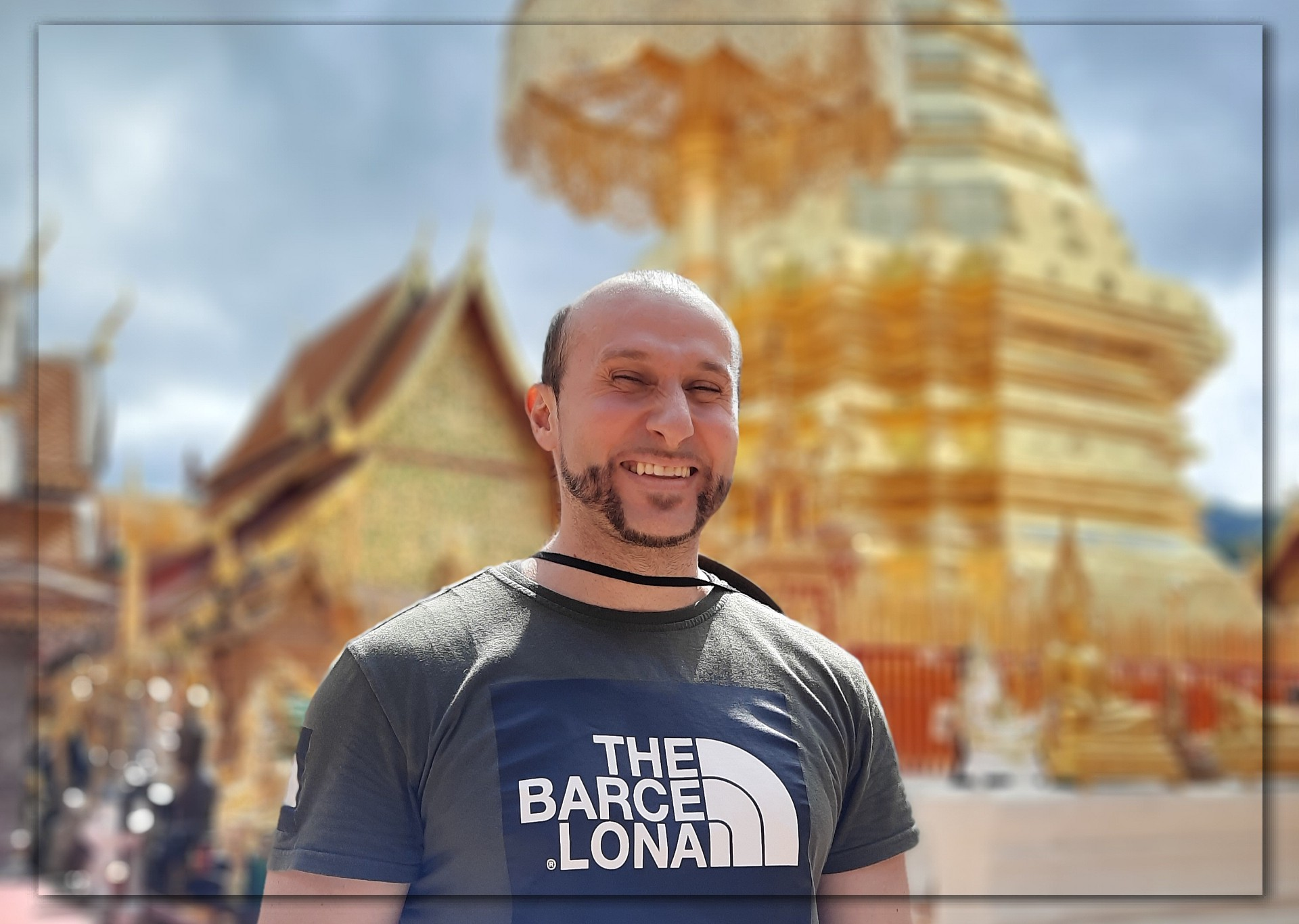 A photograph of me candidly smiling. Behind me is the famous giant gold pagoda found at Wat Phra That Doi Suthep (temple).