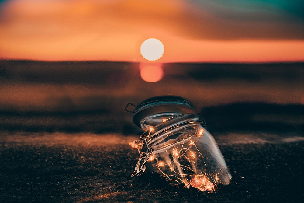 lights in a jar on the beach at sunset