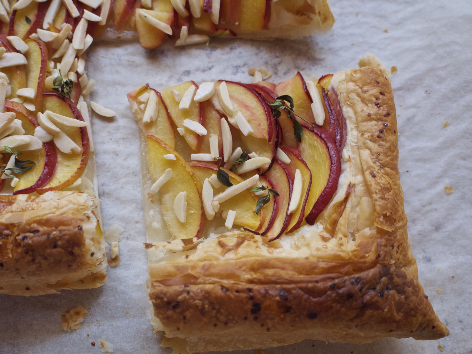 A tart topped with thinly-sliced peaches, sprinkled with slivered almonds.
