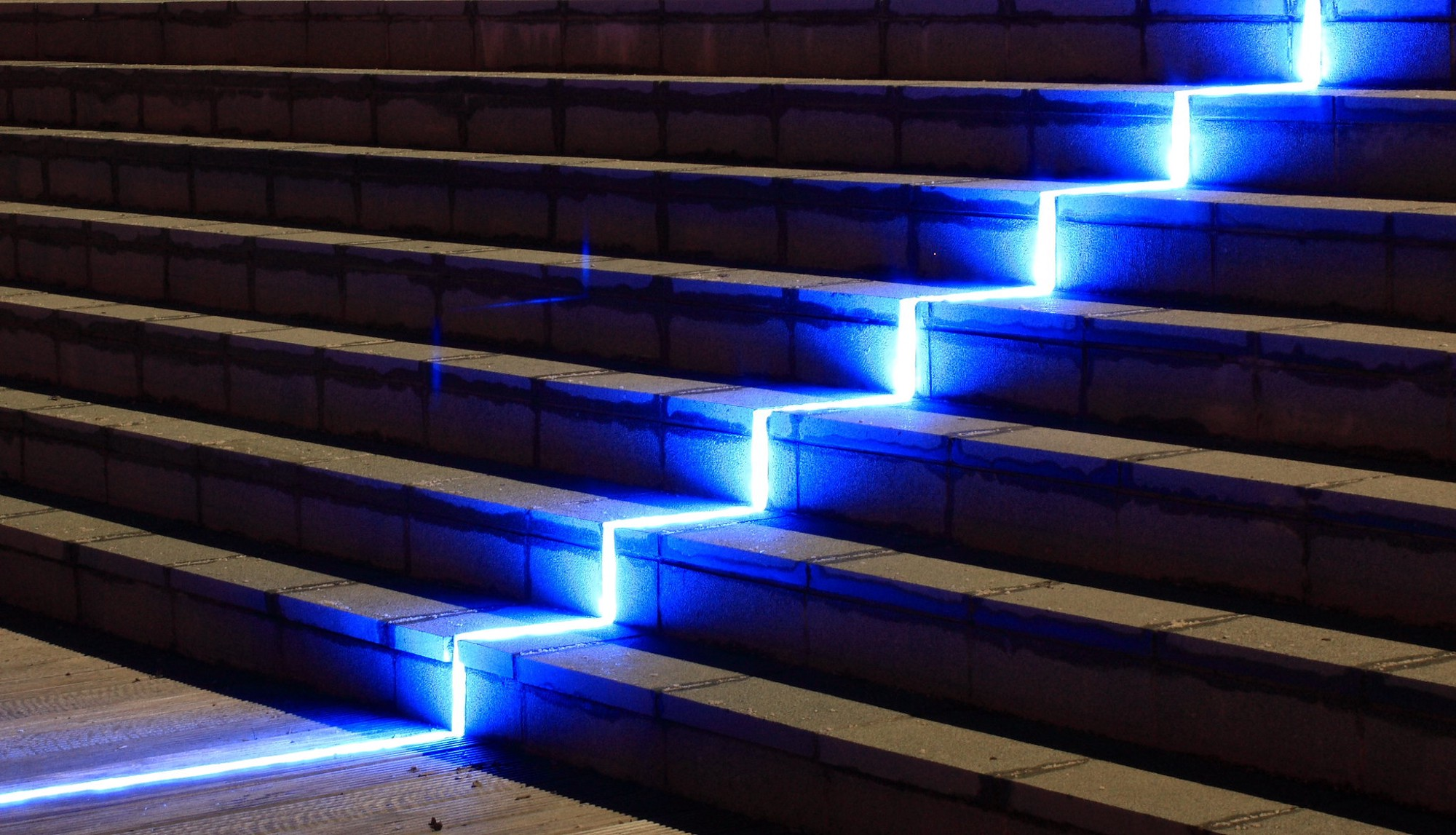 Neon light travelling up concrete steps