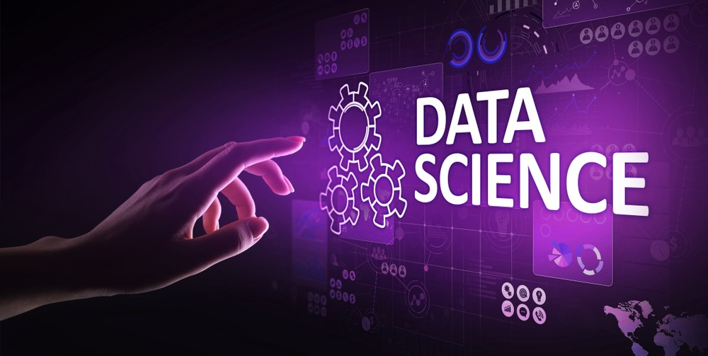 This is an image, a hand pointing at a written data science on a purple wall