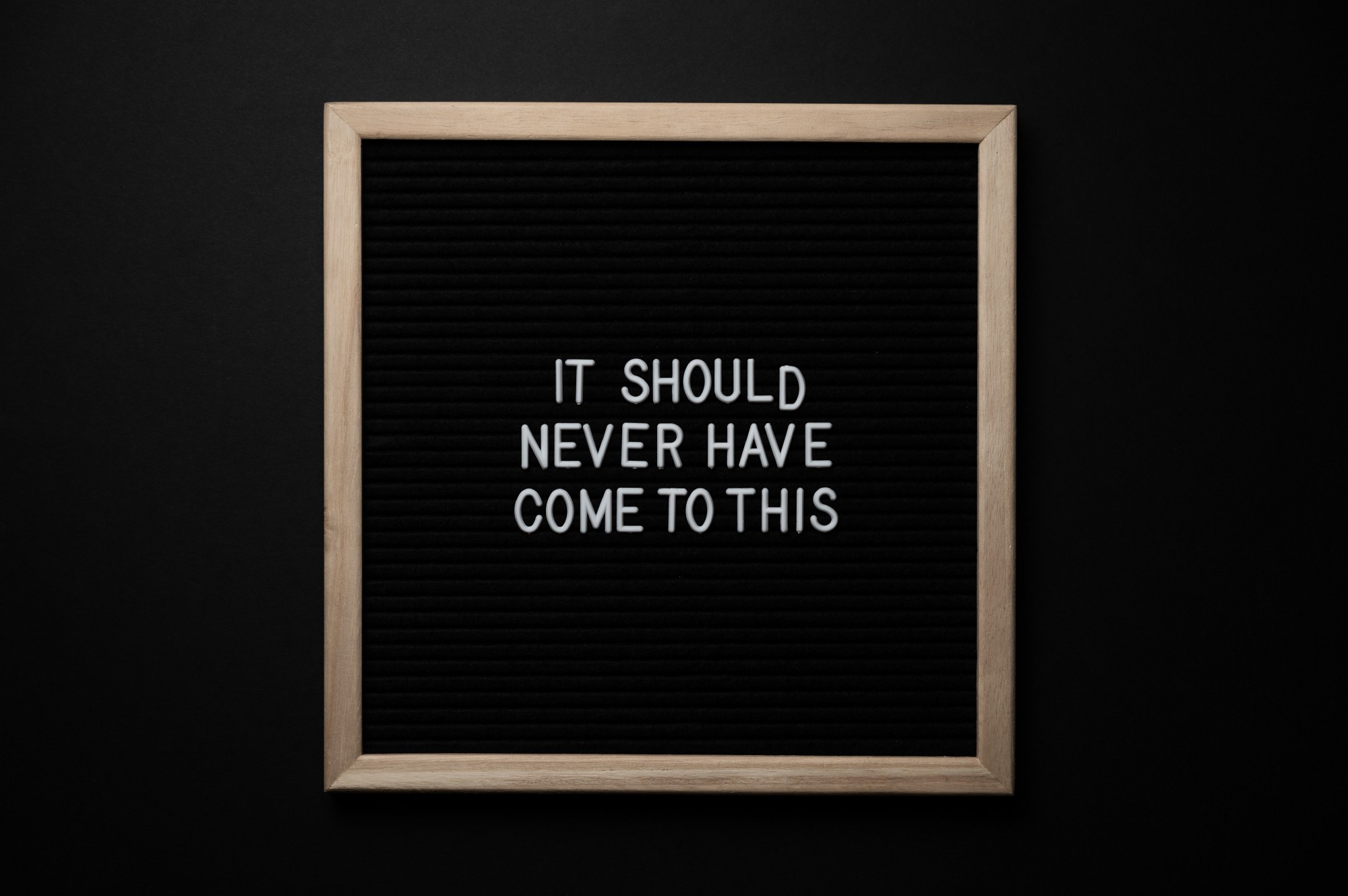 """a white text on a black chalkboard with bronze borders, saying """"It should never have come down to this."""""""