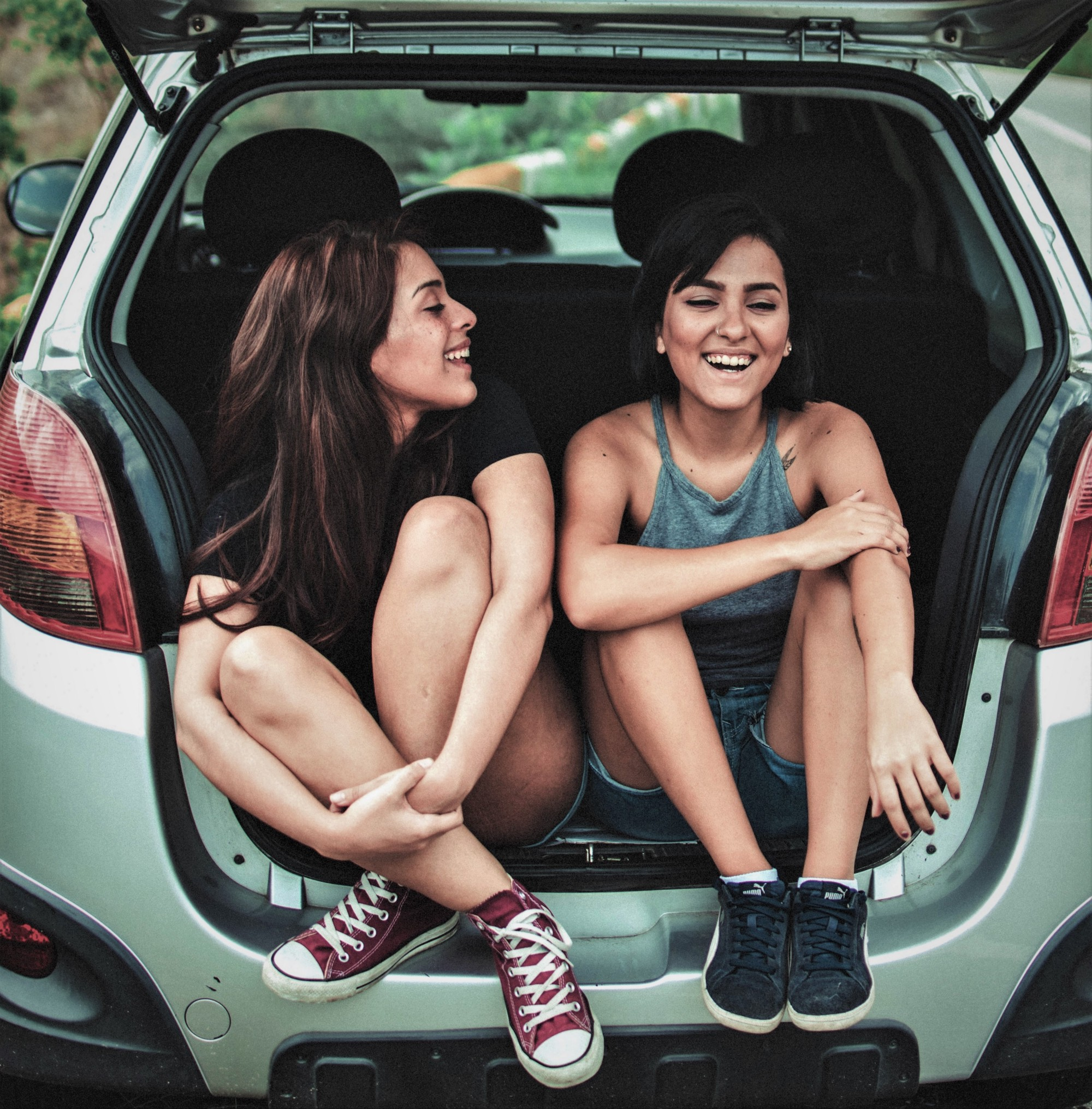 two smiling girls with brown hair sitting in open back of car