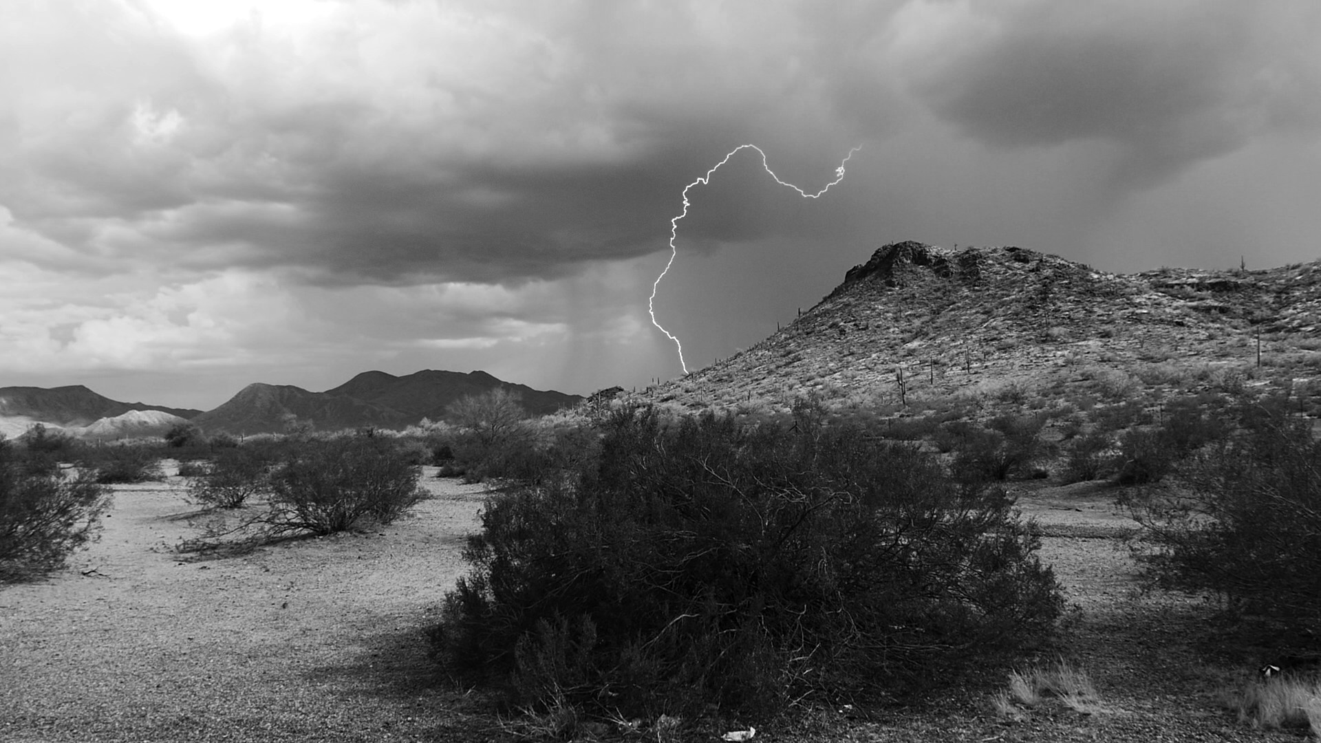 Black and white landscape photo of desert mountain range, brush, rainclouds and a bolt of lightning.