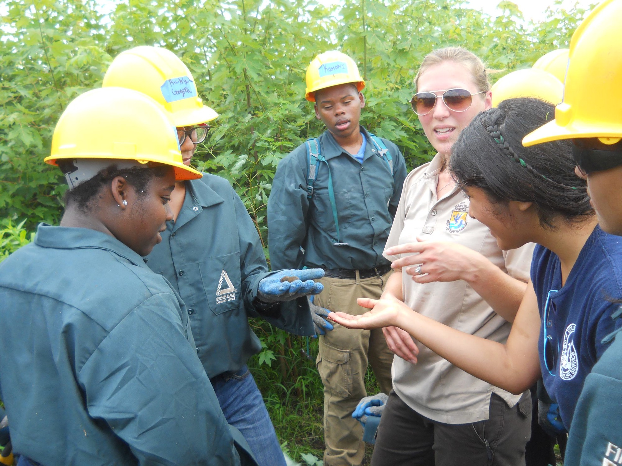 Woman in sunglasses and a Service pol talking with a group of students in hard hats and green uniform shirts outdoors