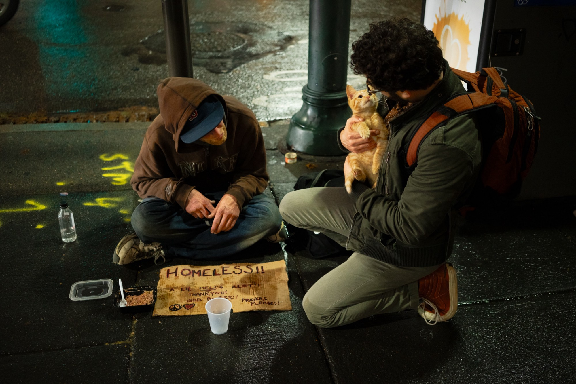 A man wearing a backpack holds an orange cat as he kneels next to a homeless person