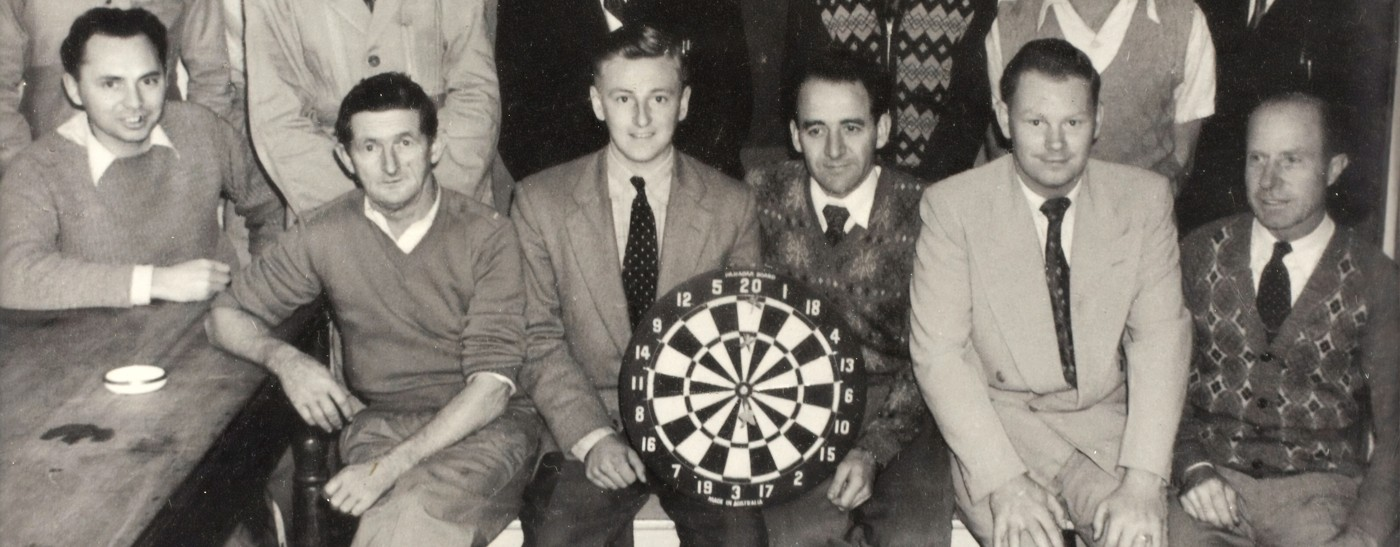 An old time picture of a dart throwing team.