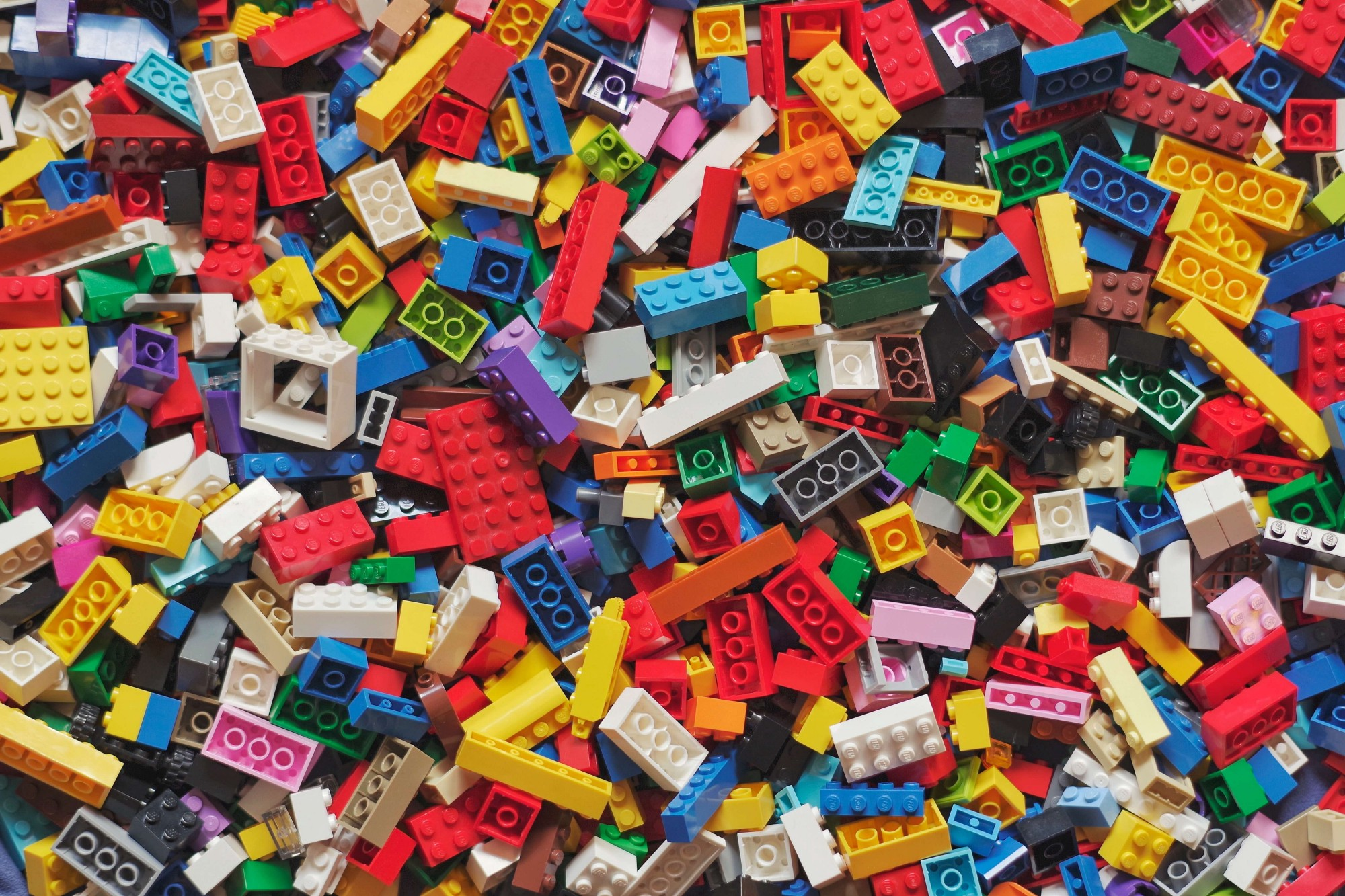 Multi-colored Lego pieces lying one on top of another.