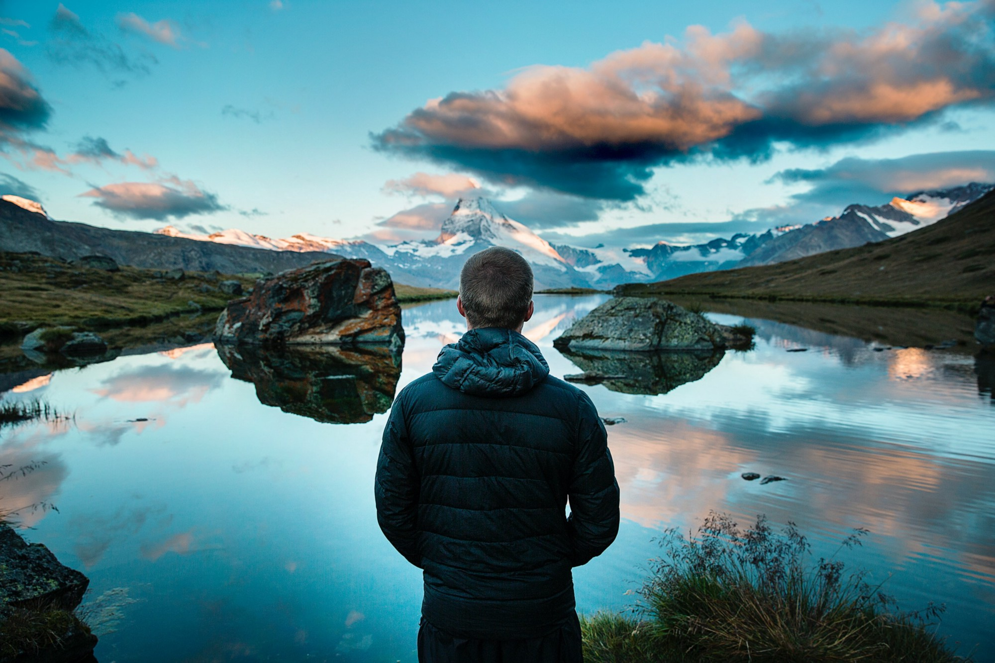 rear view of man looking out over lake with reflection of sky and clouds