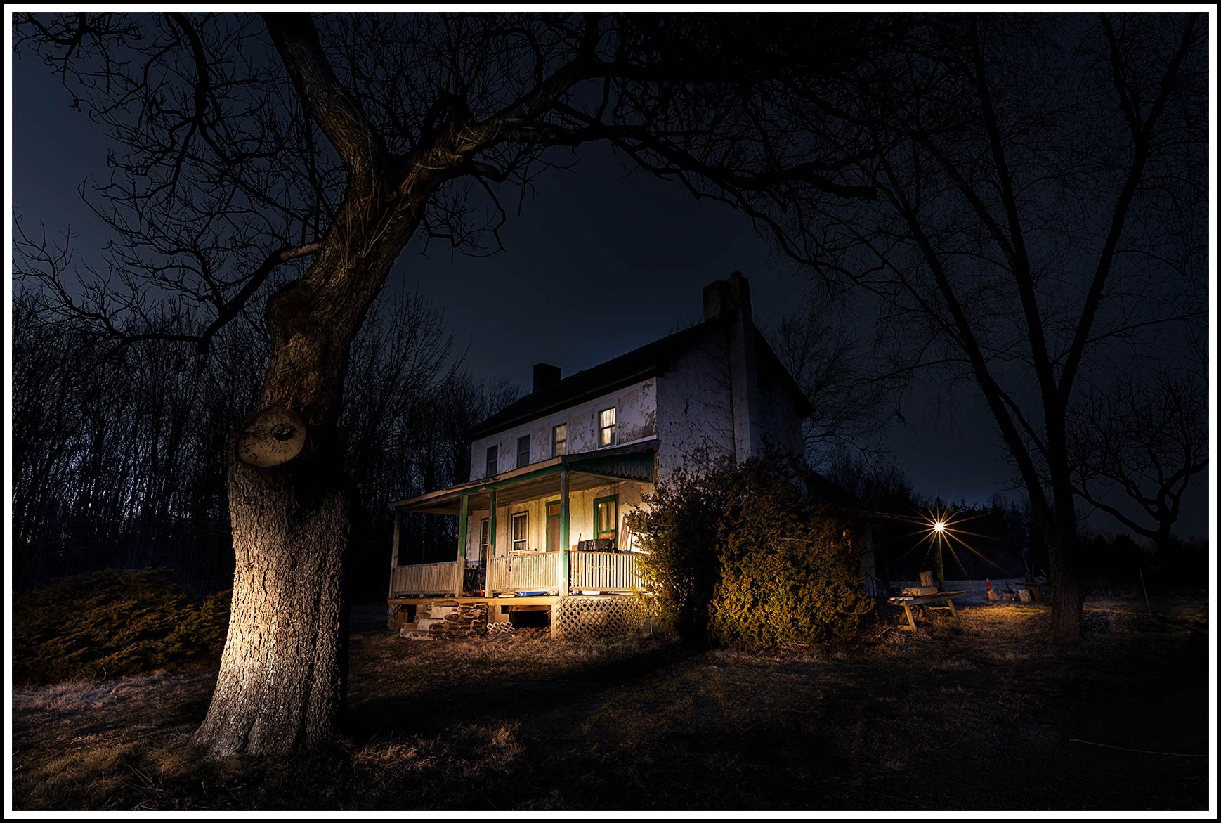 A farmhouse caught in the headlights of a car