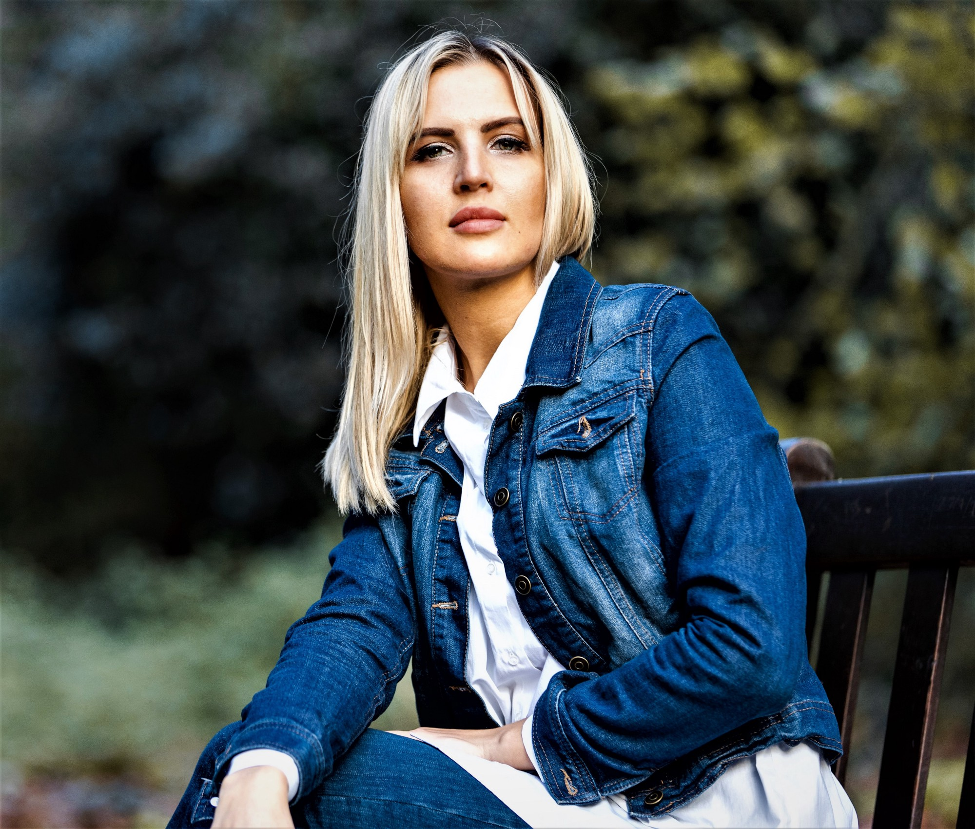 girl with long blonde hair wearing long sleeve blue denim jacket and white shirt with foliage background