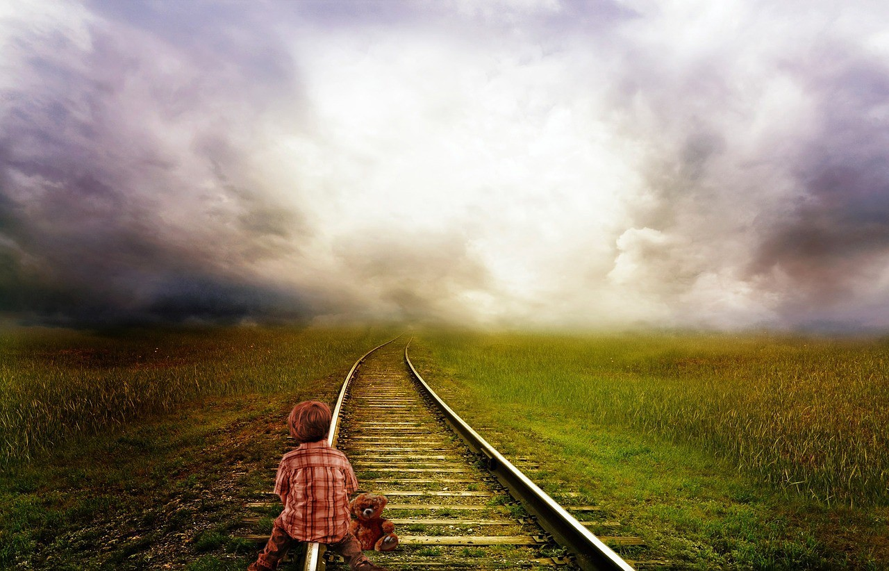 A young child sits looking away into the distance on railway tracks with a teddy bear at their side. The tracks are on grass and disappear into the clouds.