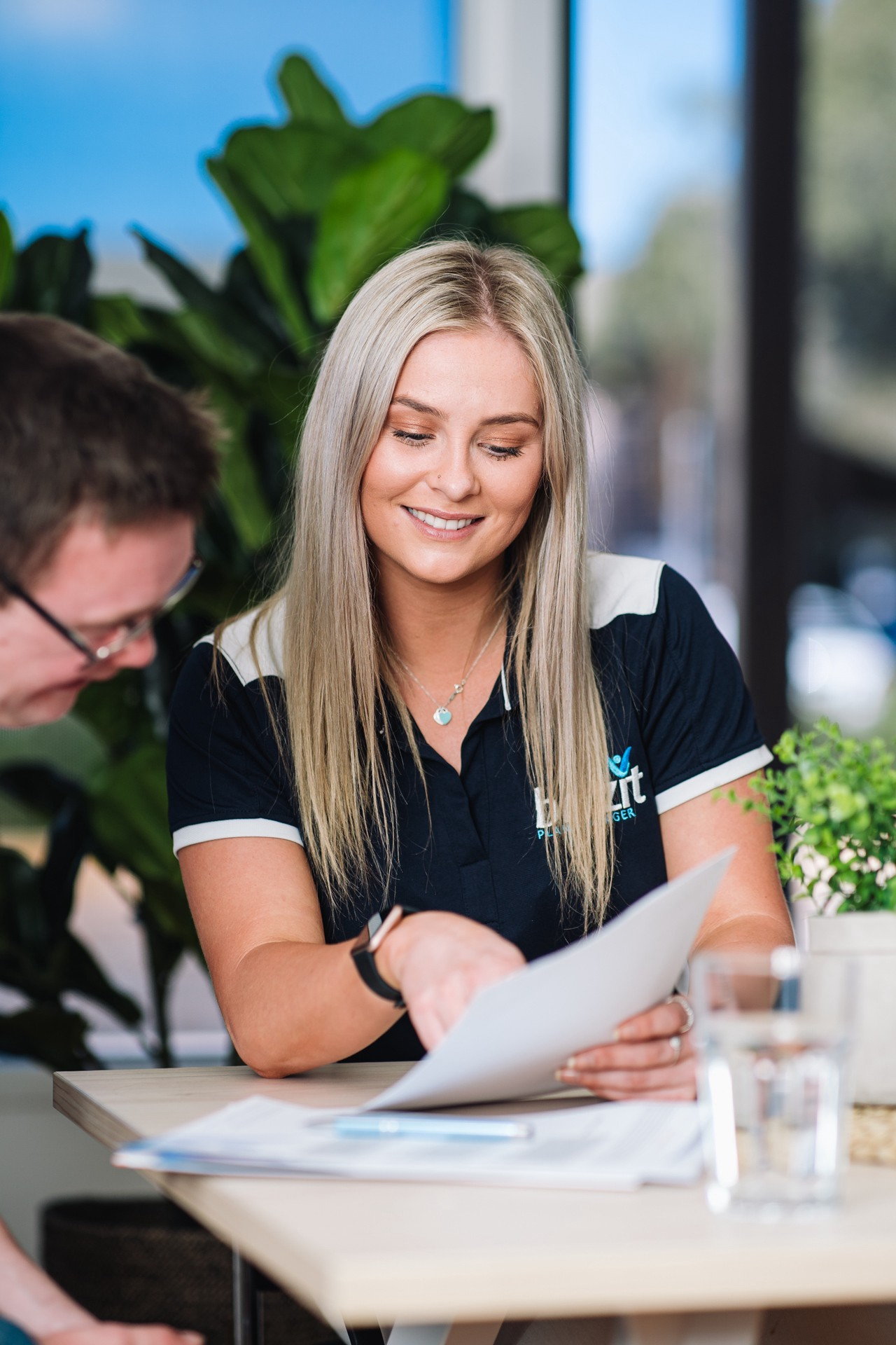 A female Blitzit staff member with long blonde hair wears a Navy & white Blitzit shirt, while guiding a participant through their Service Agreement. The participant is male, with short brown hair and glasses.