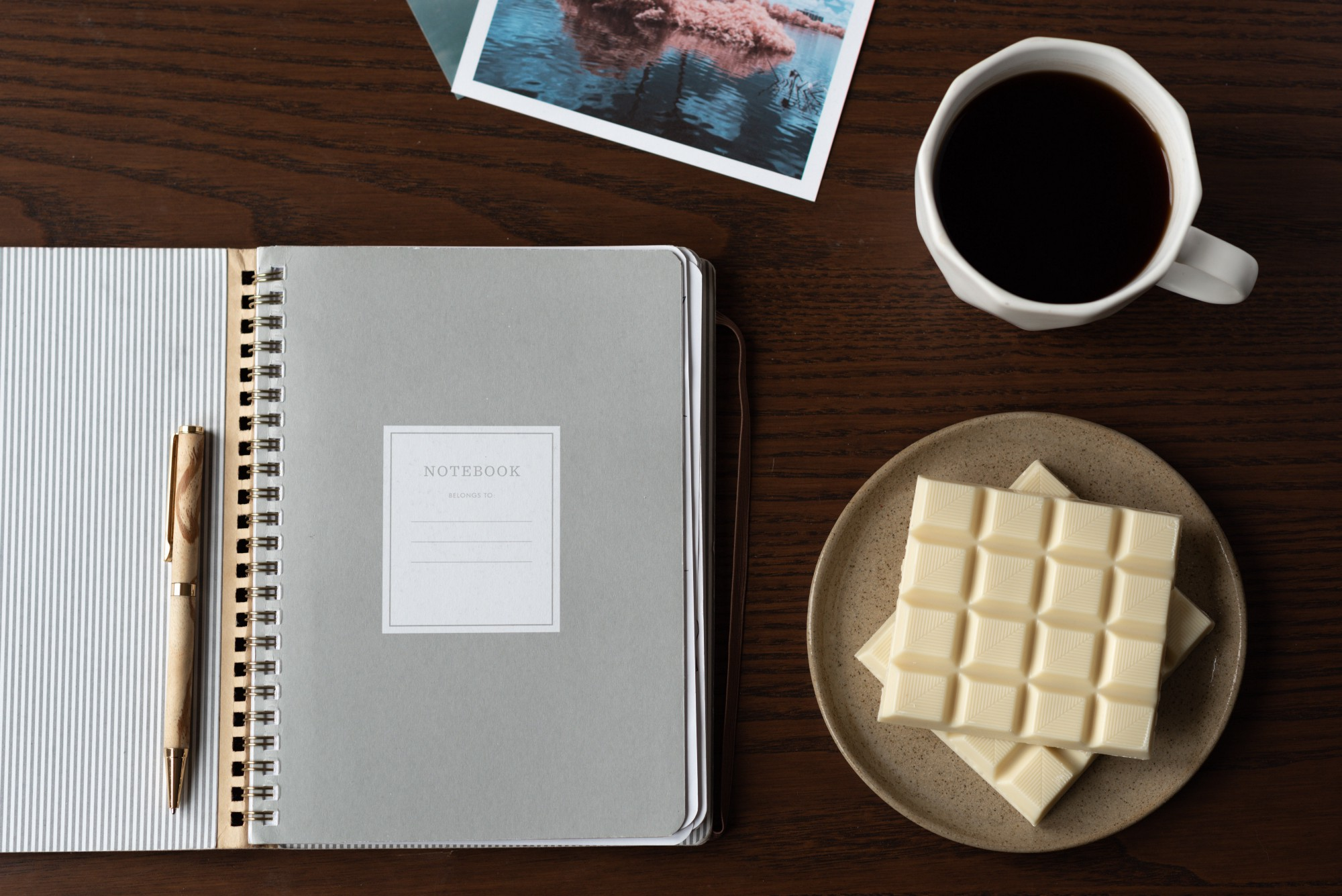 An open notebook laid out on a wooden table with chocolate, coffee, and a picture book.
