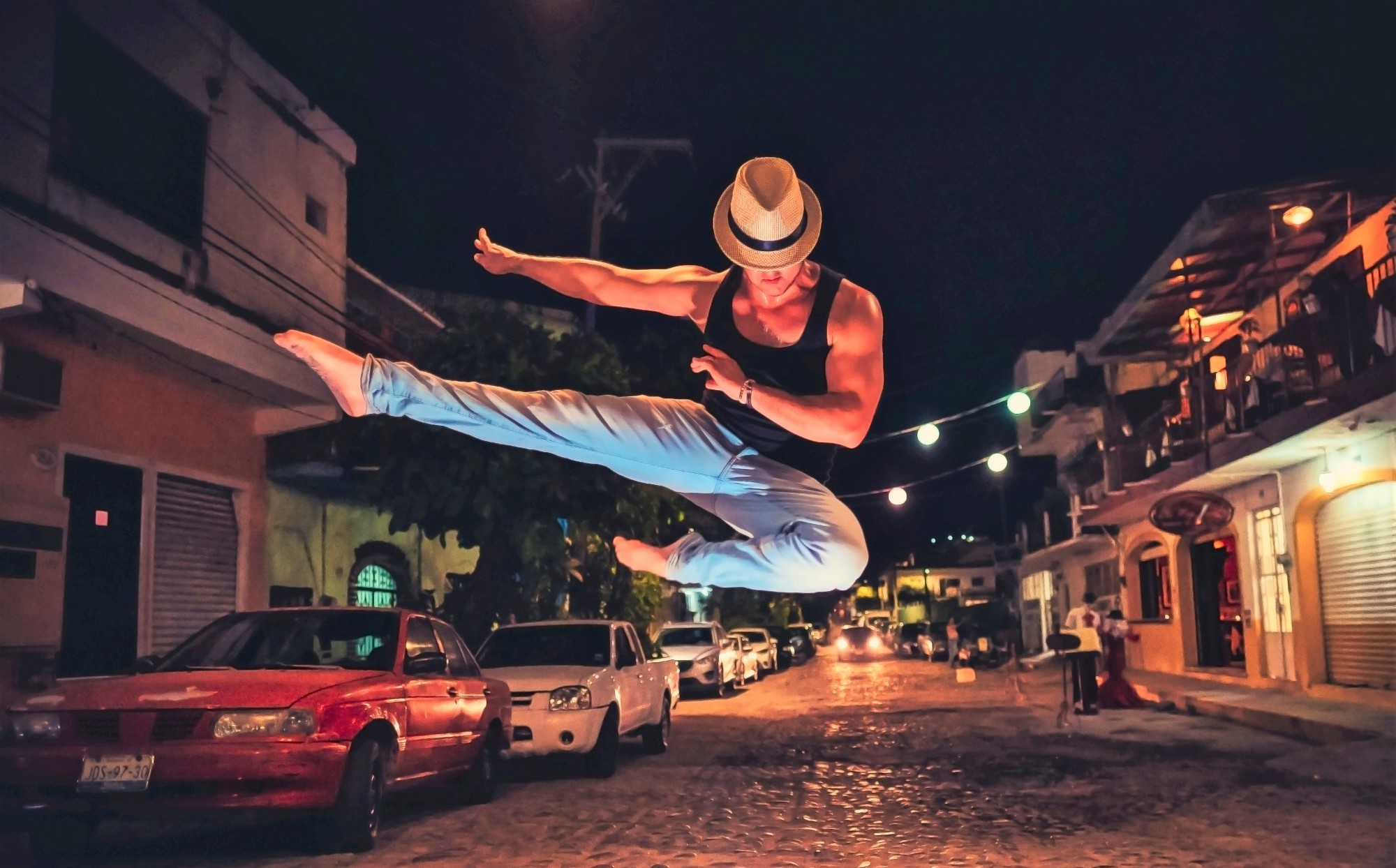 Man wearing hat, black shirt, blue jeans leaping in the air in middle of cobblestone street