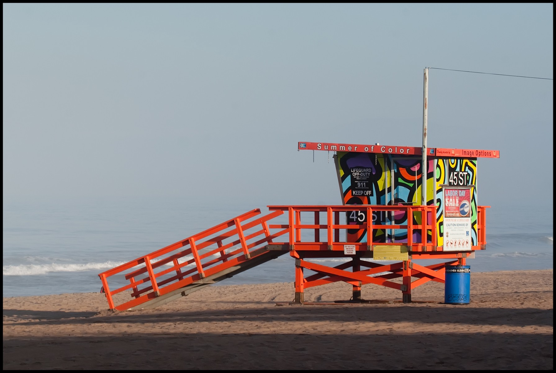 Photo of colourfully-painted lifeguard tower on calm, unpeopled beach.