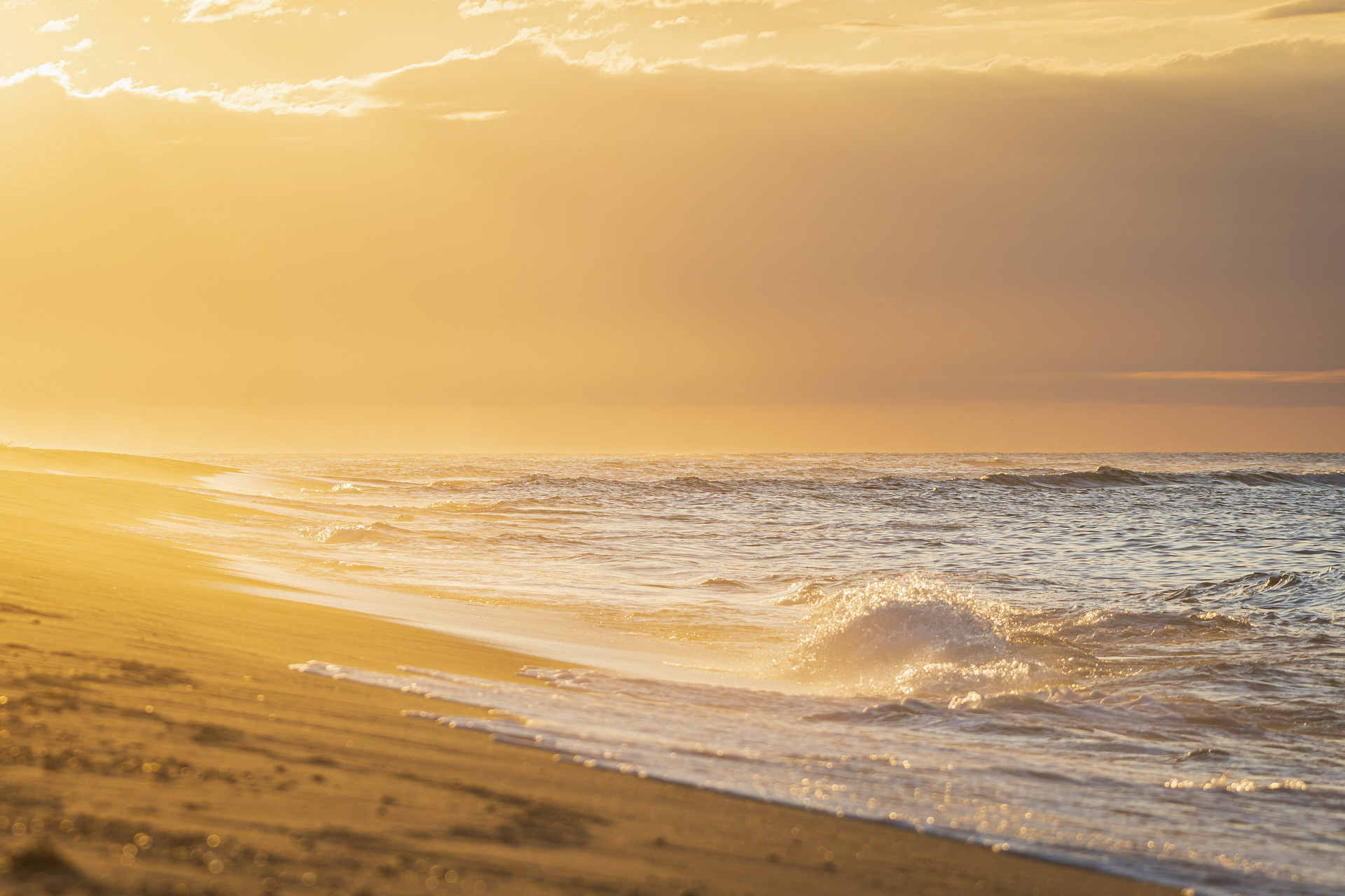Sandy beach at sunrise. Gentle waves lapping at the shore against a backdrop of clouds