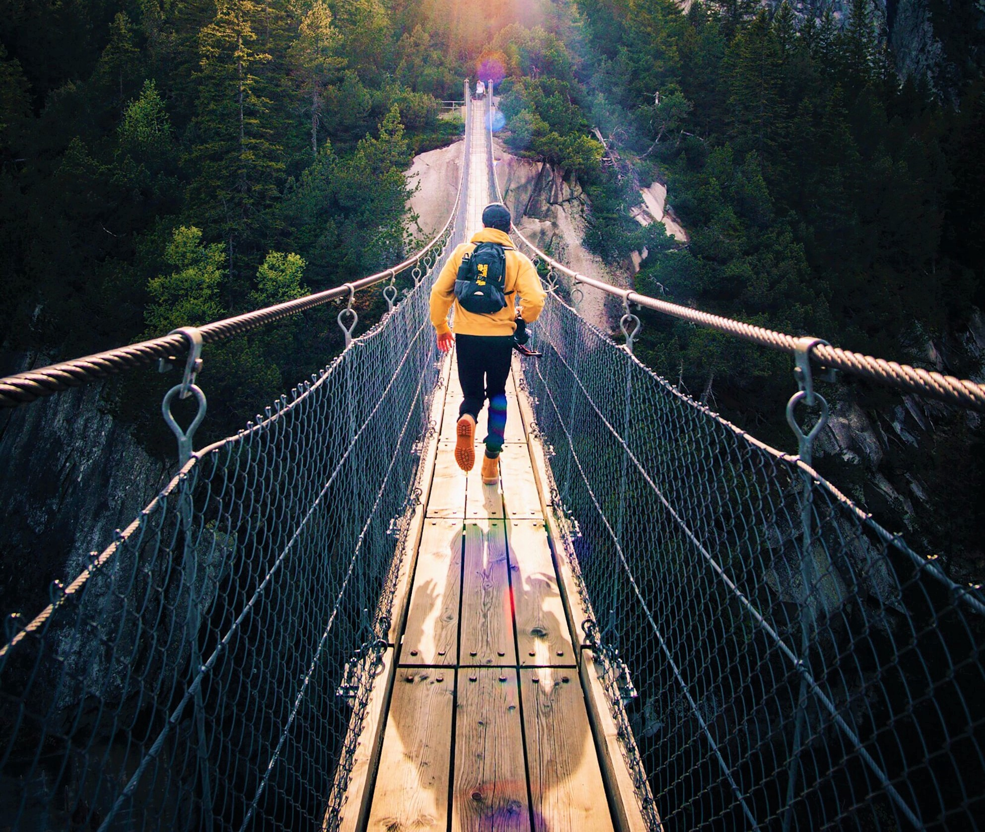 back view of man wearing yellow jacket and backpack running across suspension bridge