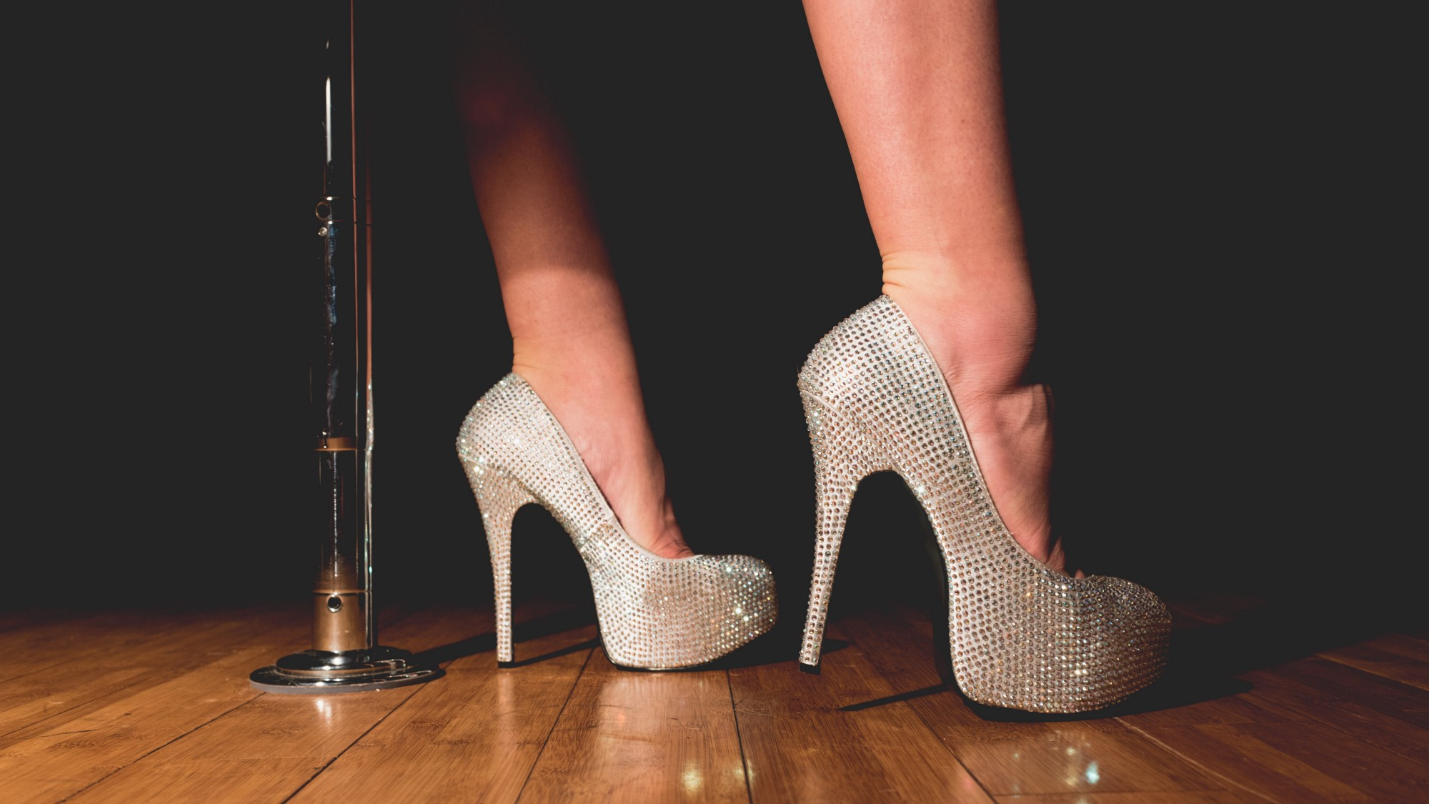 A shot of a woman's feet in stiletto high heels covered with rhinestones, standing next to a pole