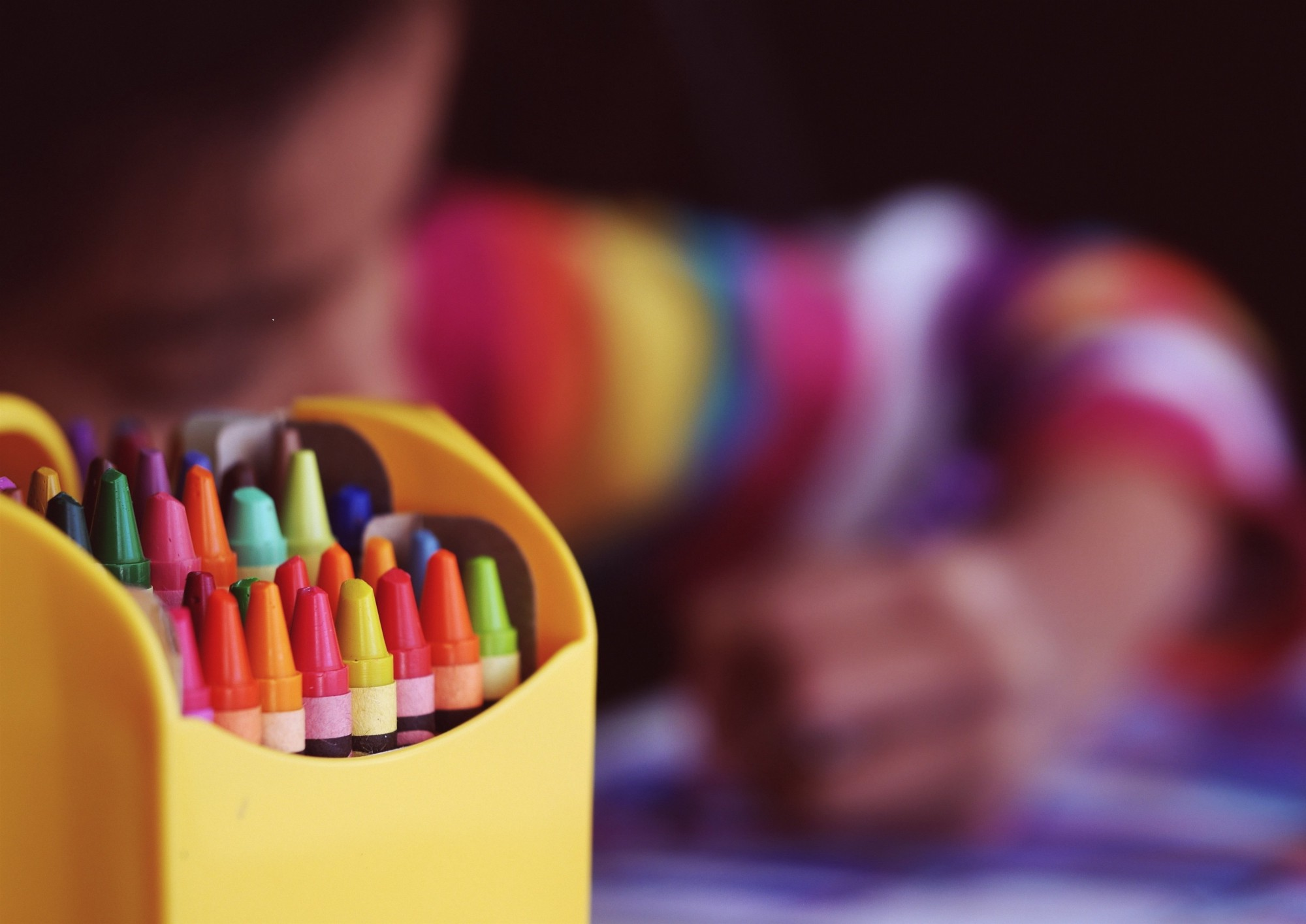 A child colors with crayons