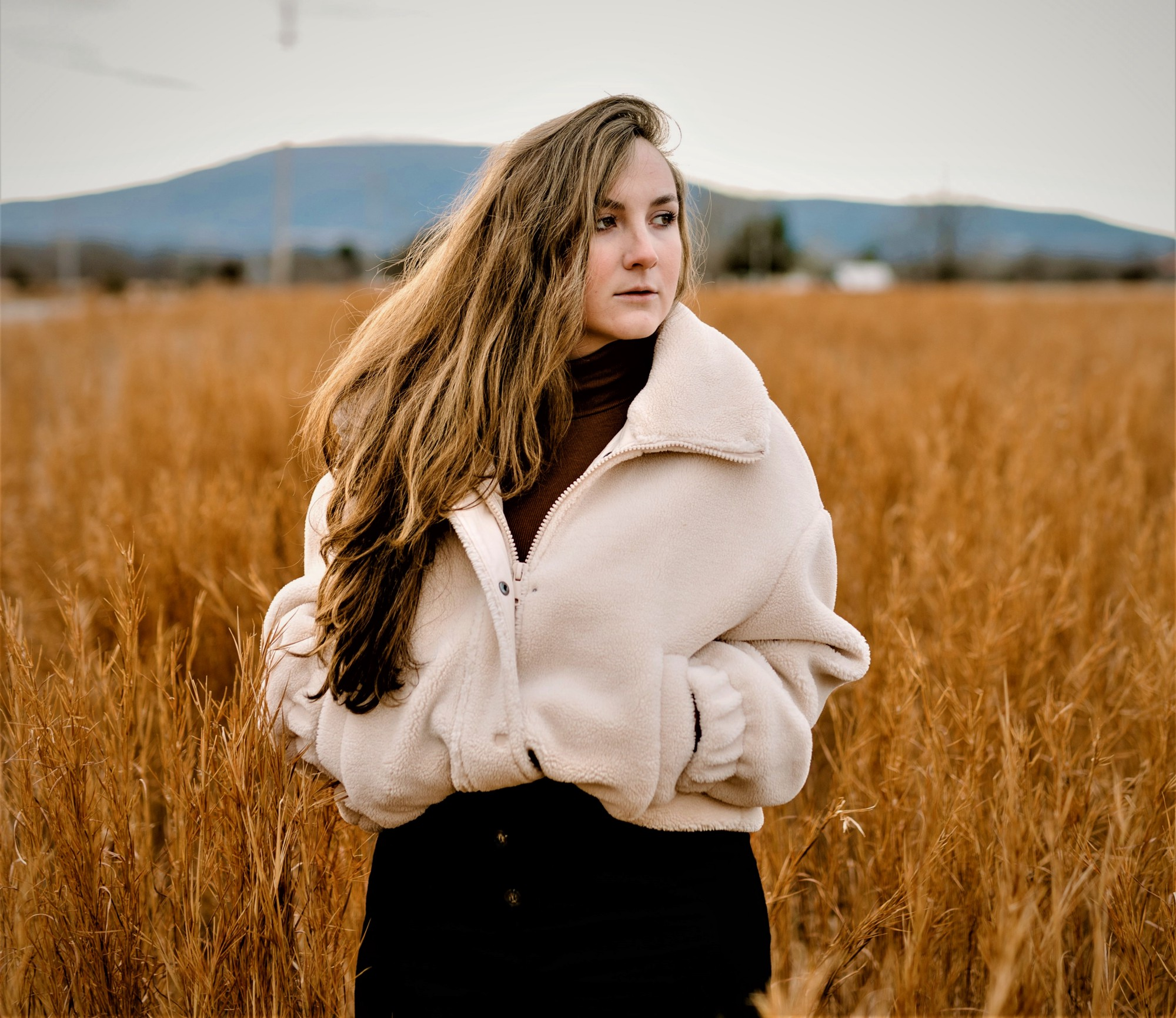 girl with long brown hair wearing white furry coat looking off in the distance