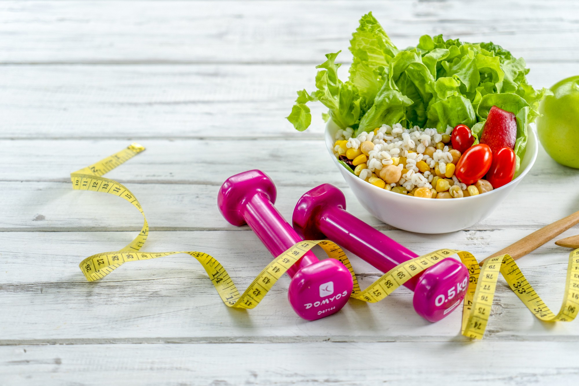 Two .5 kg dumbbells, measuring tape, and a salad on a rustic wooden table.