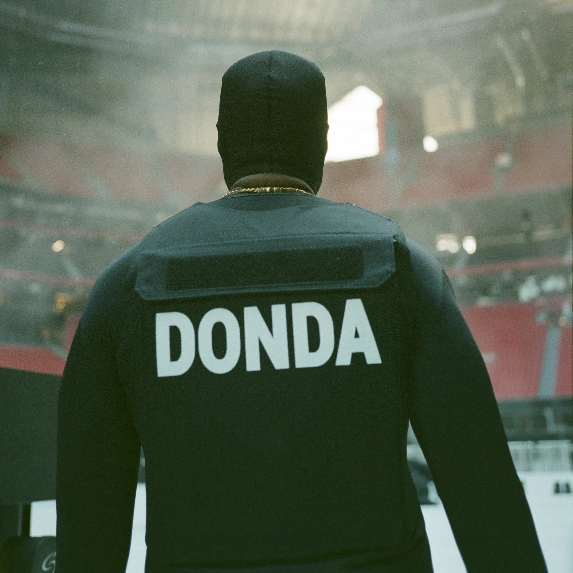 Rapper Kanye West In all black with his back to the camera, sporting a vest with Donda emblazoned at the back