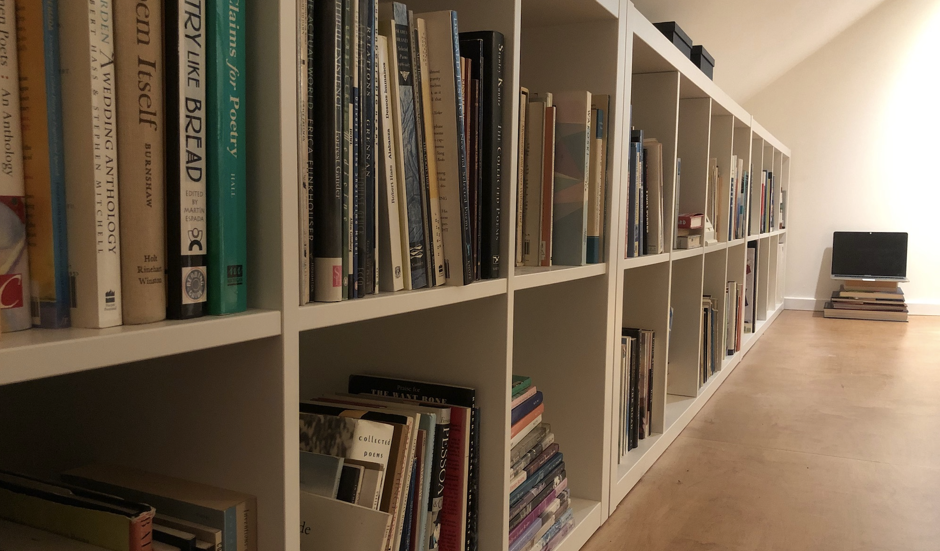 A long bookshelf full of books with a computer laptop at one end