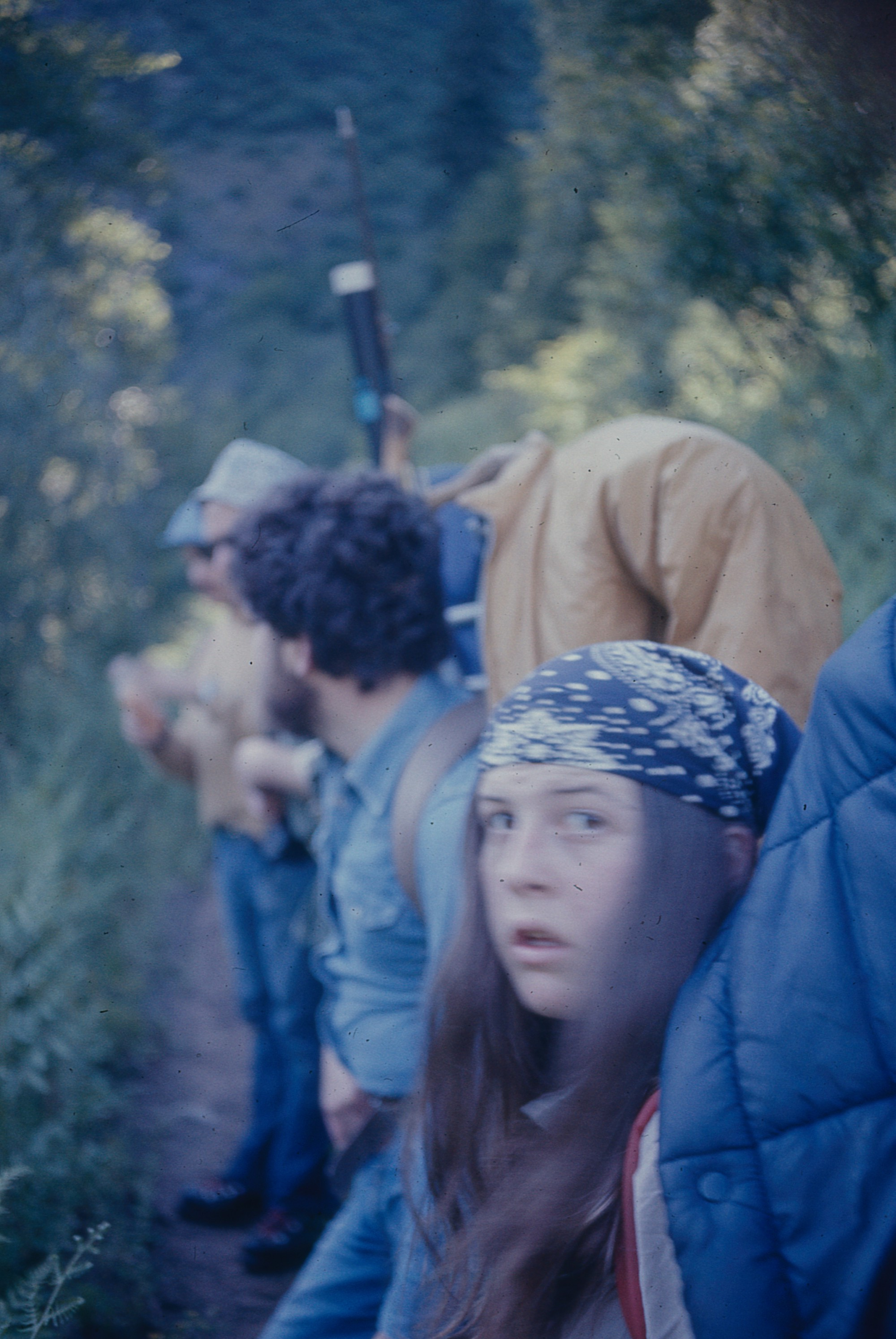 Teenage irl with long brown hair wearing a bandnana scarf and carrying a back pack with a coat over it, looking back at the camera with two other backpakers behind her.