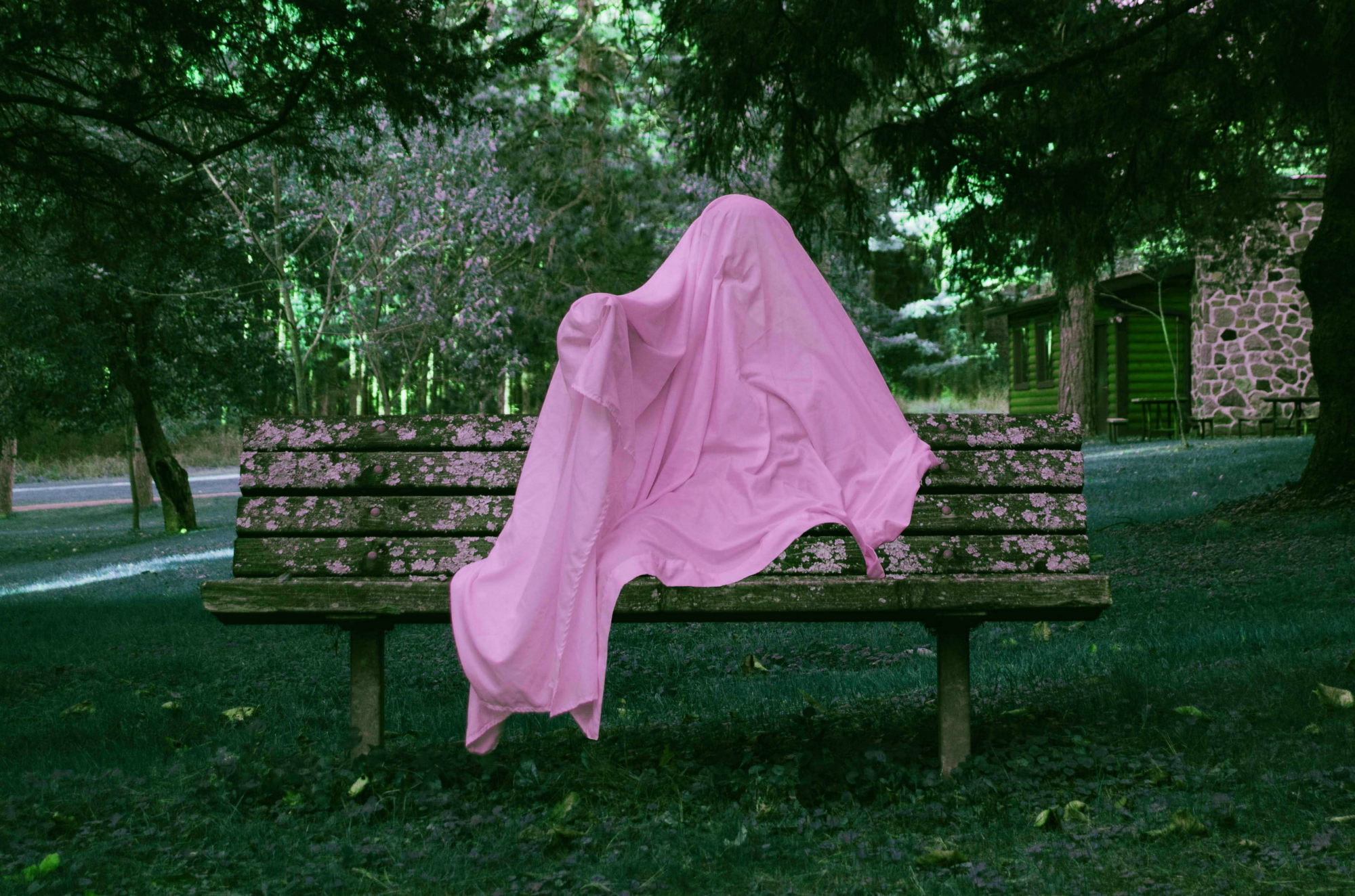 Person sitting underneath a pink sheet on a bench