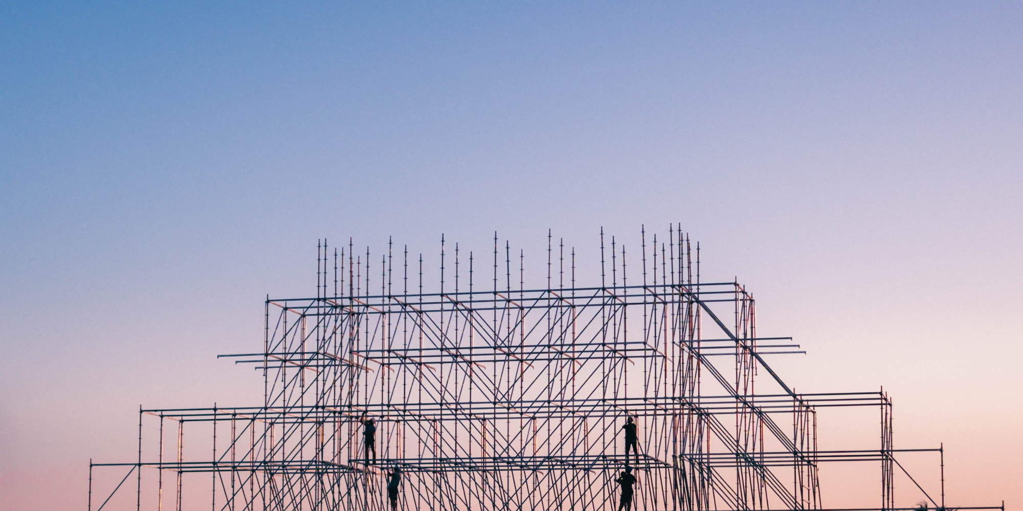 [Photo] Silhouette of four people on a steel-frame building construction.