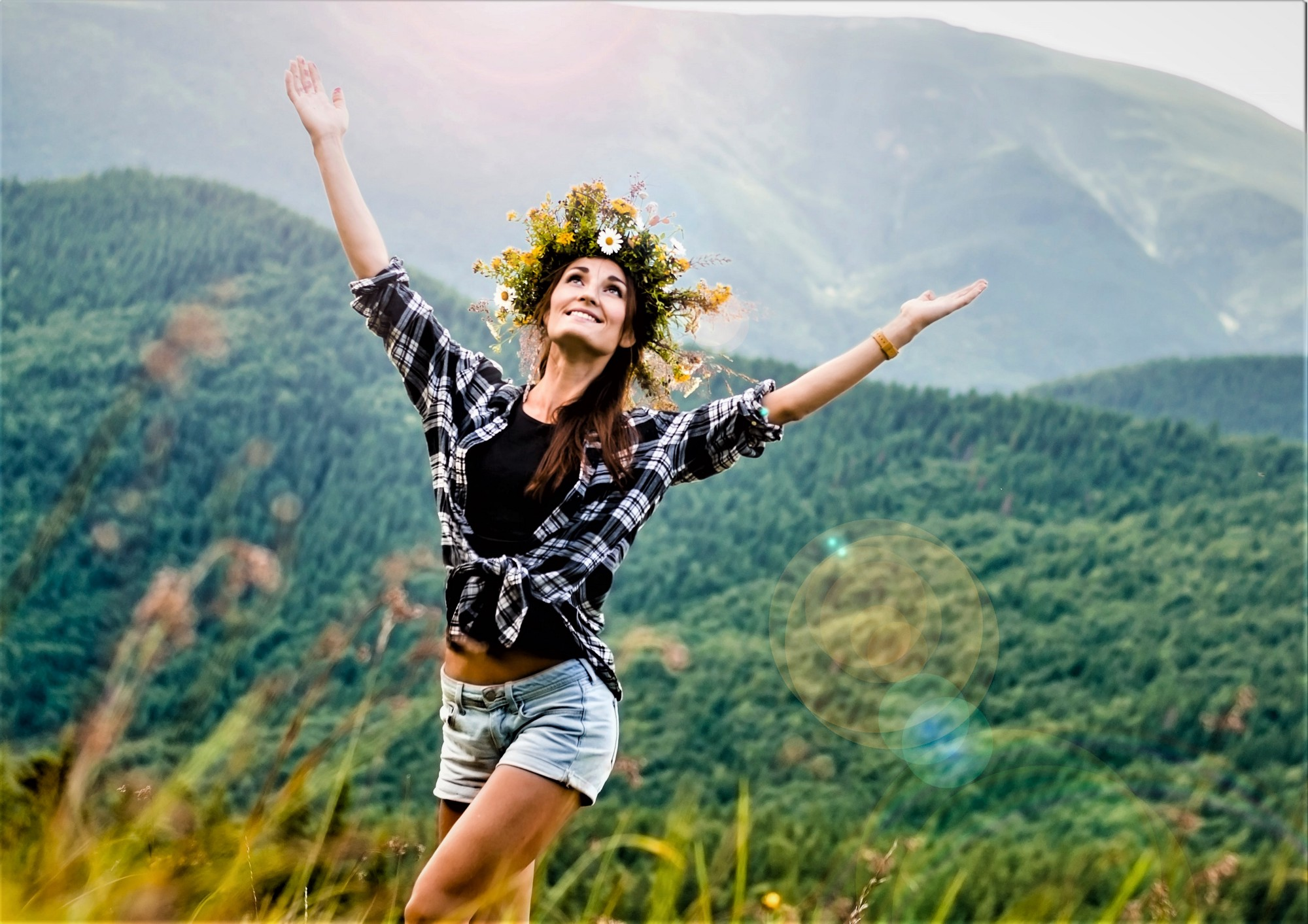 girl with long brown hair wearing wreath of flower on her head waling through grassy field with hands upraised