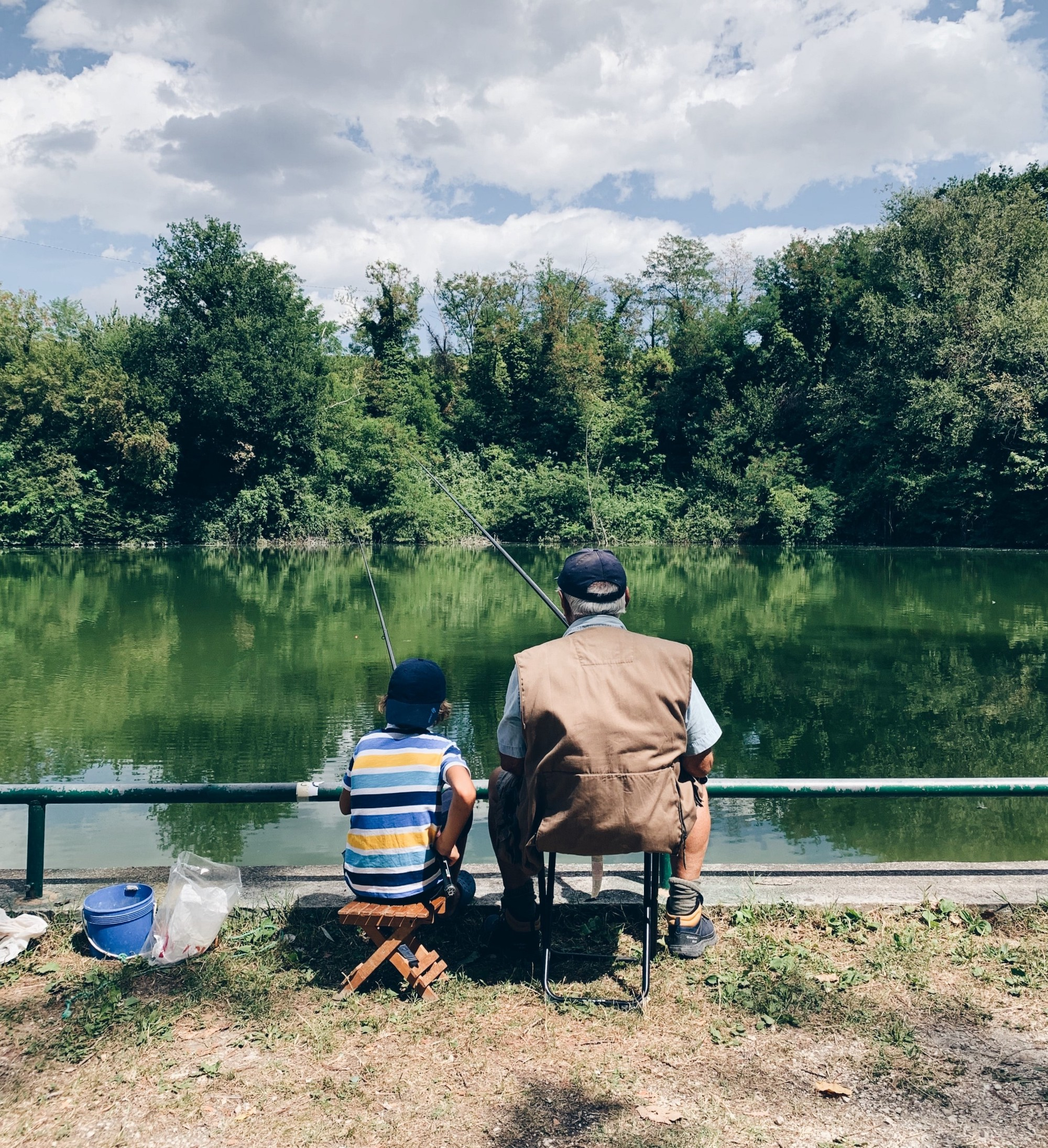 An older man sits fishing with a young child.