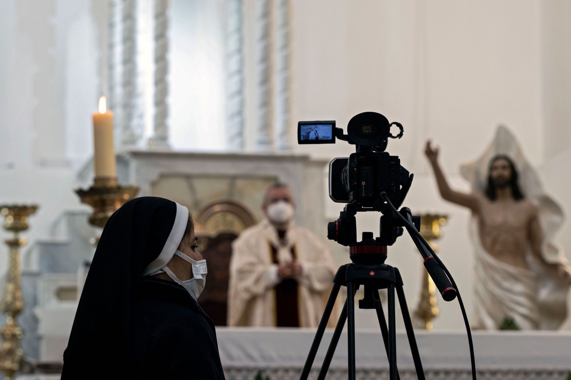 A nun with a video camera on a tripod recording a priest holding the Eucharist at an altar next to a statue of Jesus.
