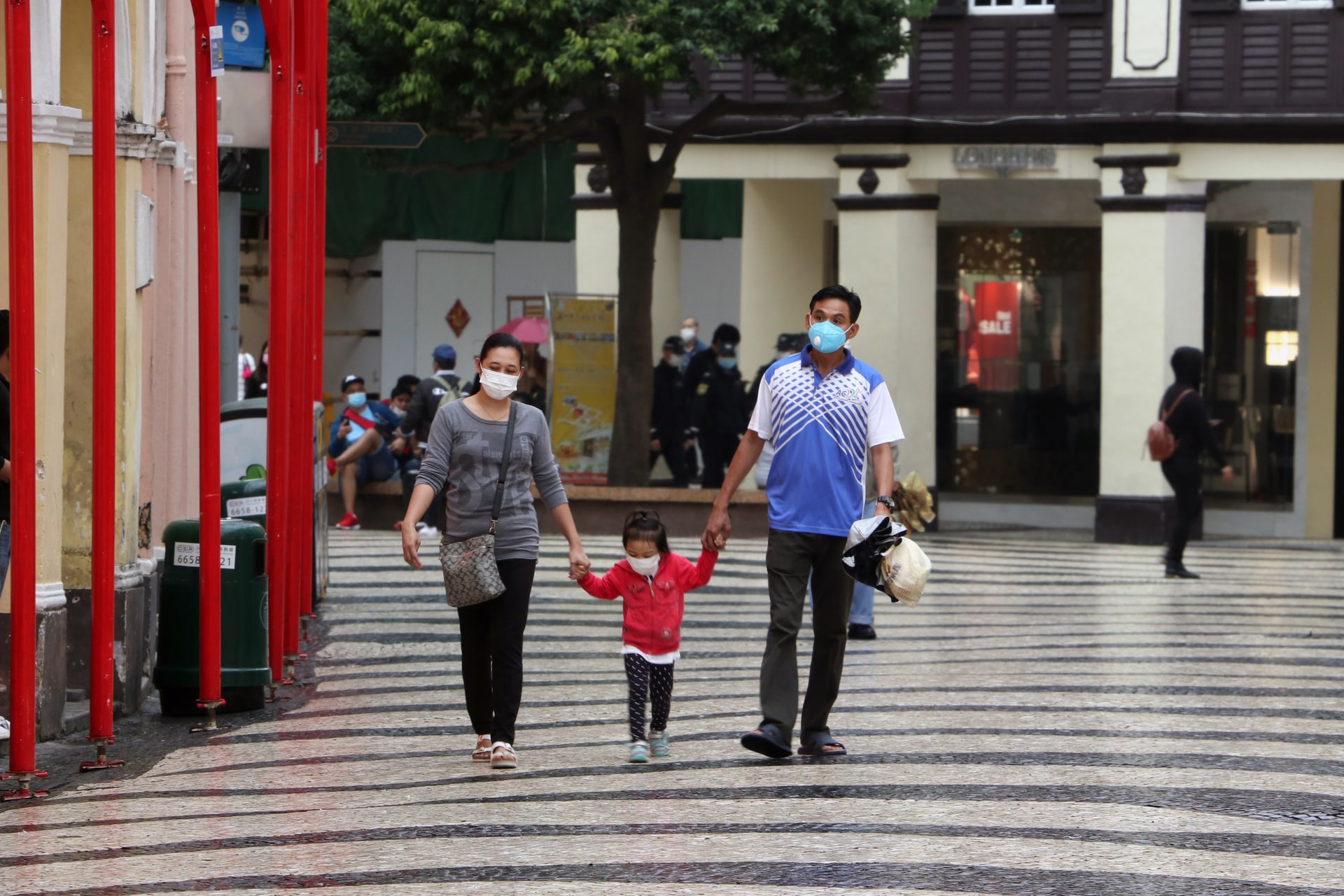 A couple and their child walk down the street, wearing masks and holding hands