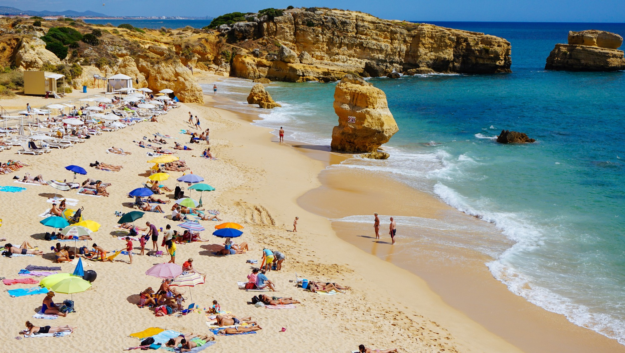 Picture of a beach (Portugal) with people and umbrellas.