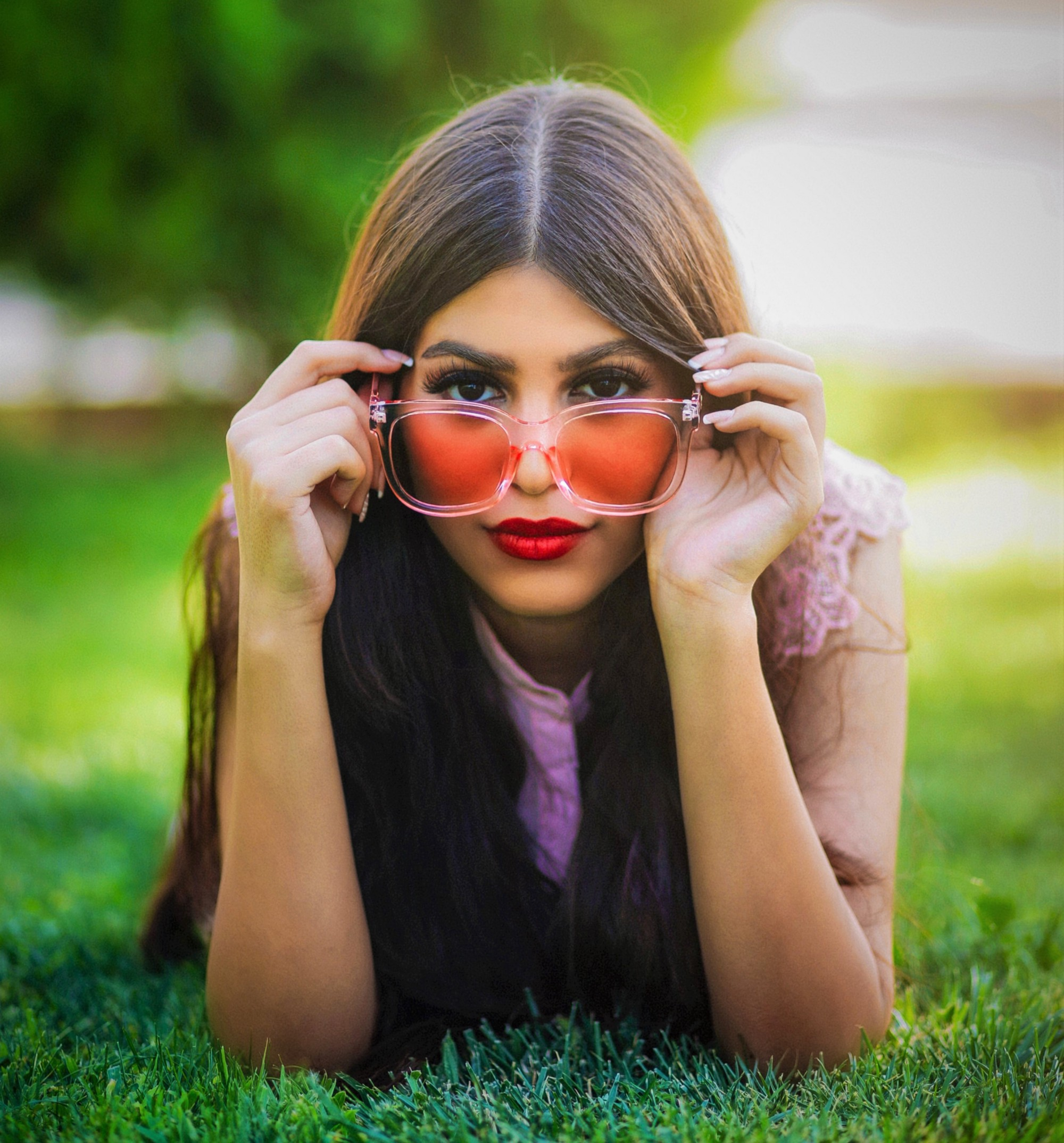 girl with long brown hair wearing tinted glasses laying on the grass