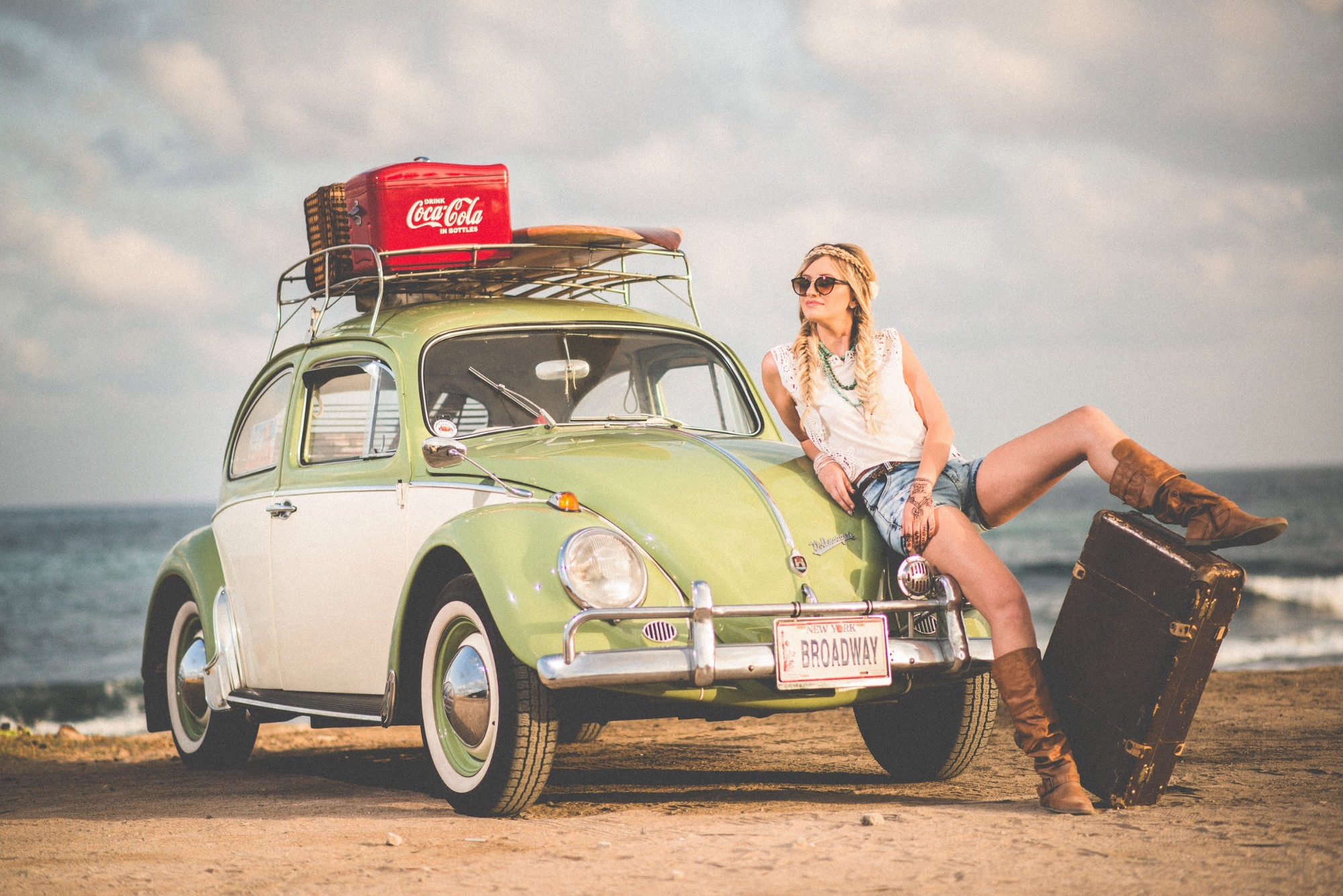 Woman leaning on green and white Volkswagen Beetle with luggage near seaside.