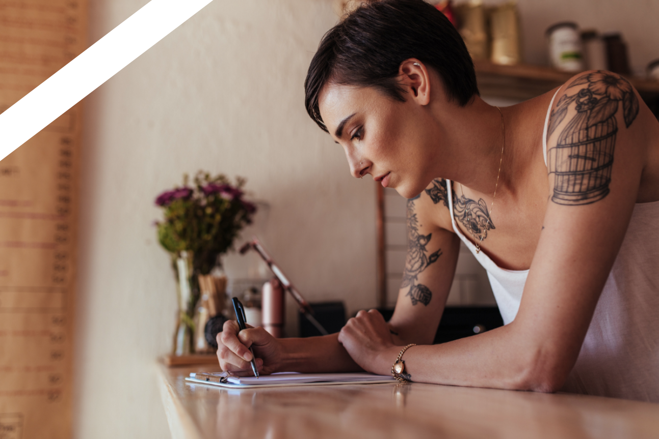 woman with arm tattoos writing at desk