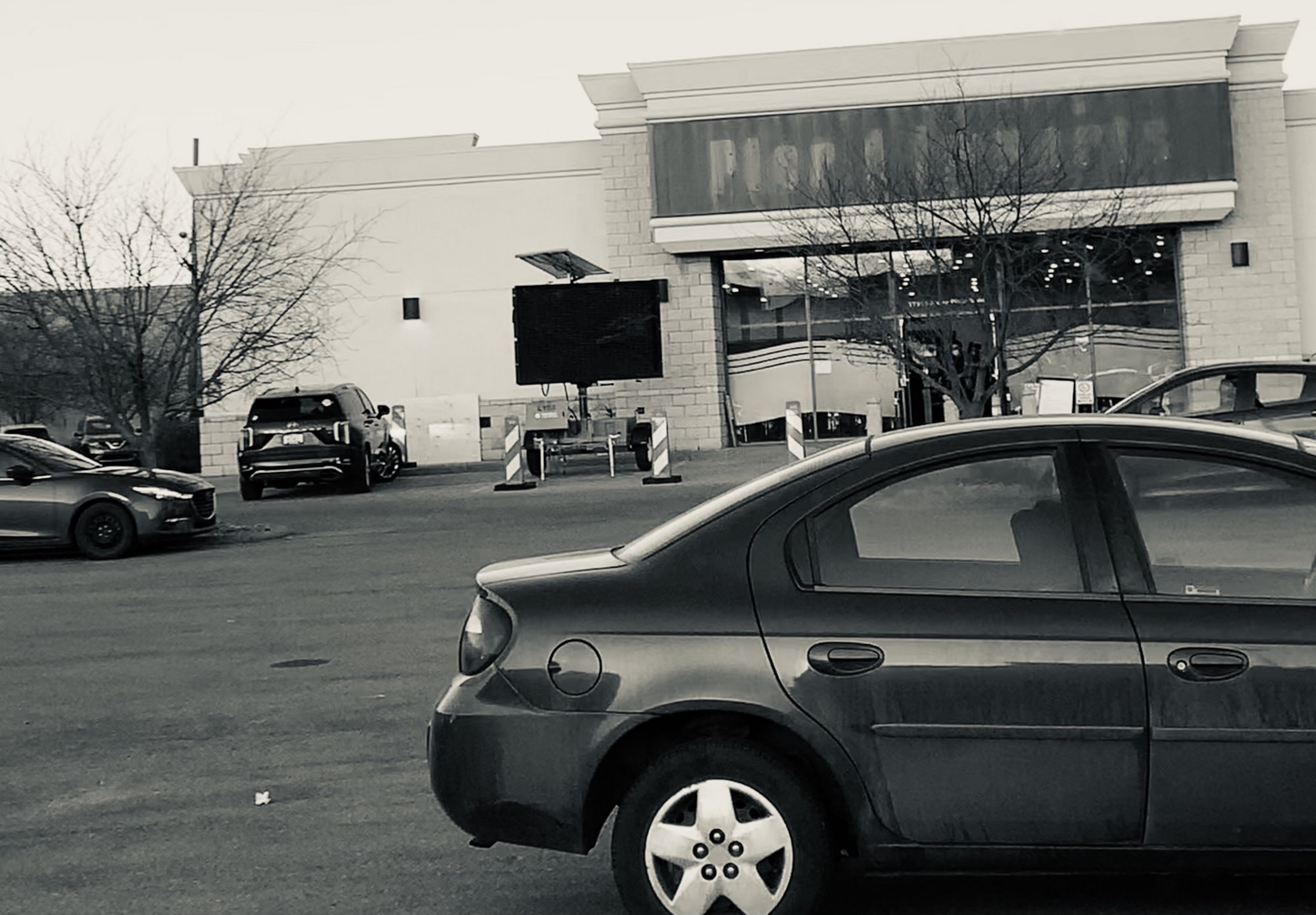 "From the perspective of a parking lot, a drab, black and white photo of a building that used to be a ""Pier 1"" store, now being utilized as a vaccination station."