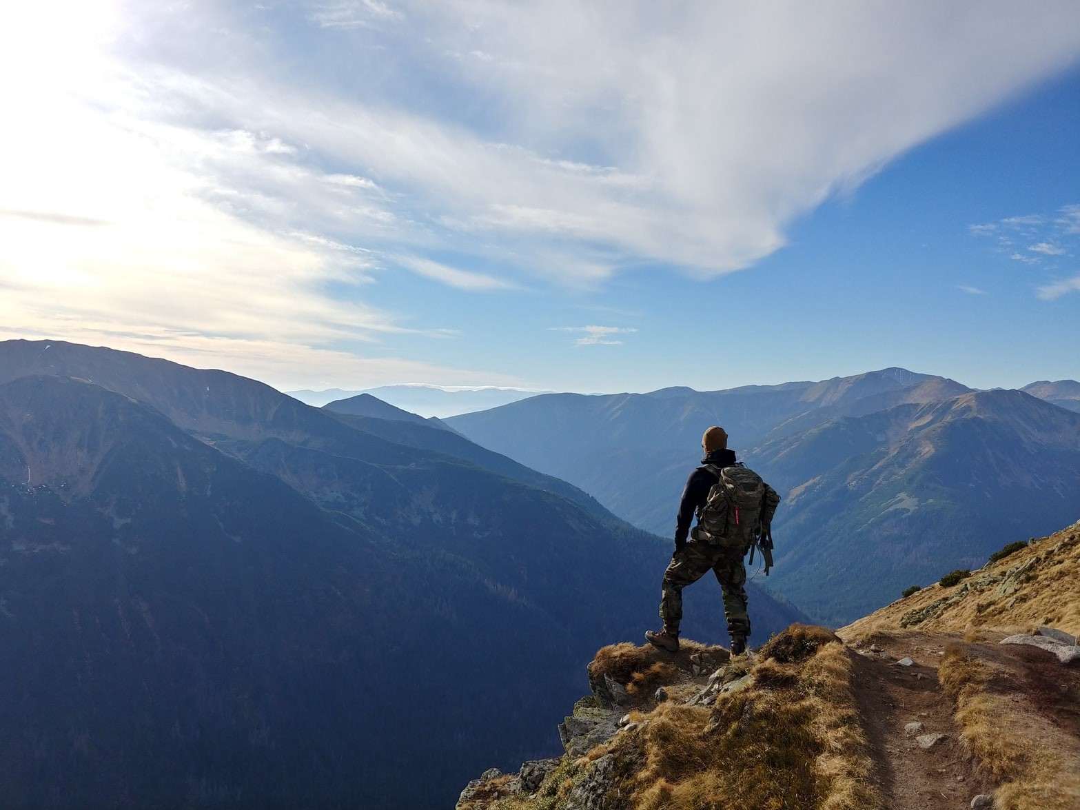 Hiker standing on moountain looking at a scenic valley and mountain scape
