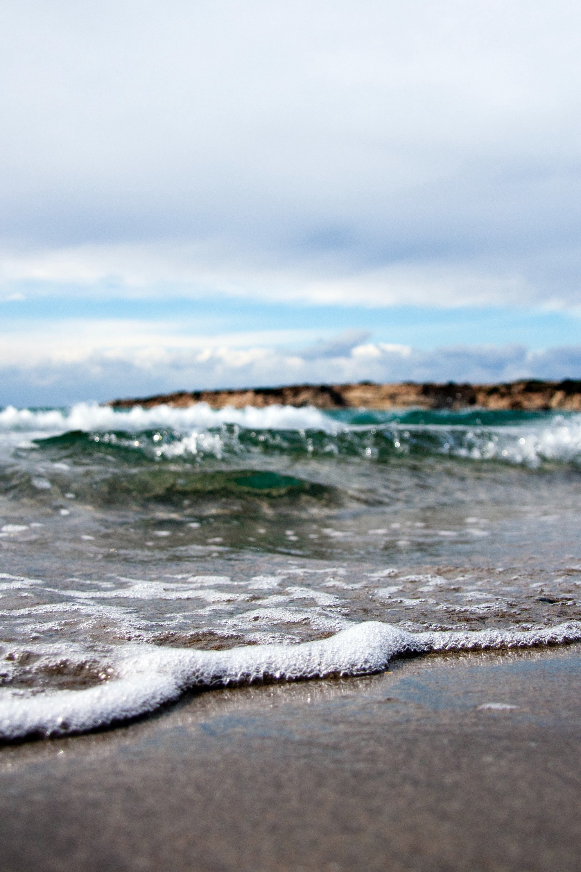 Image at ground level of the ocean coming onto the shore
