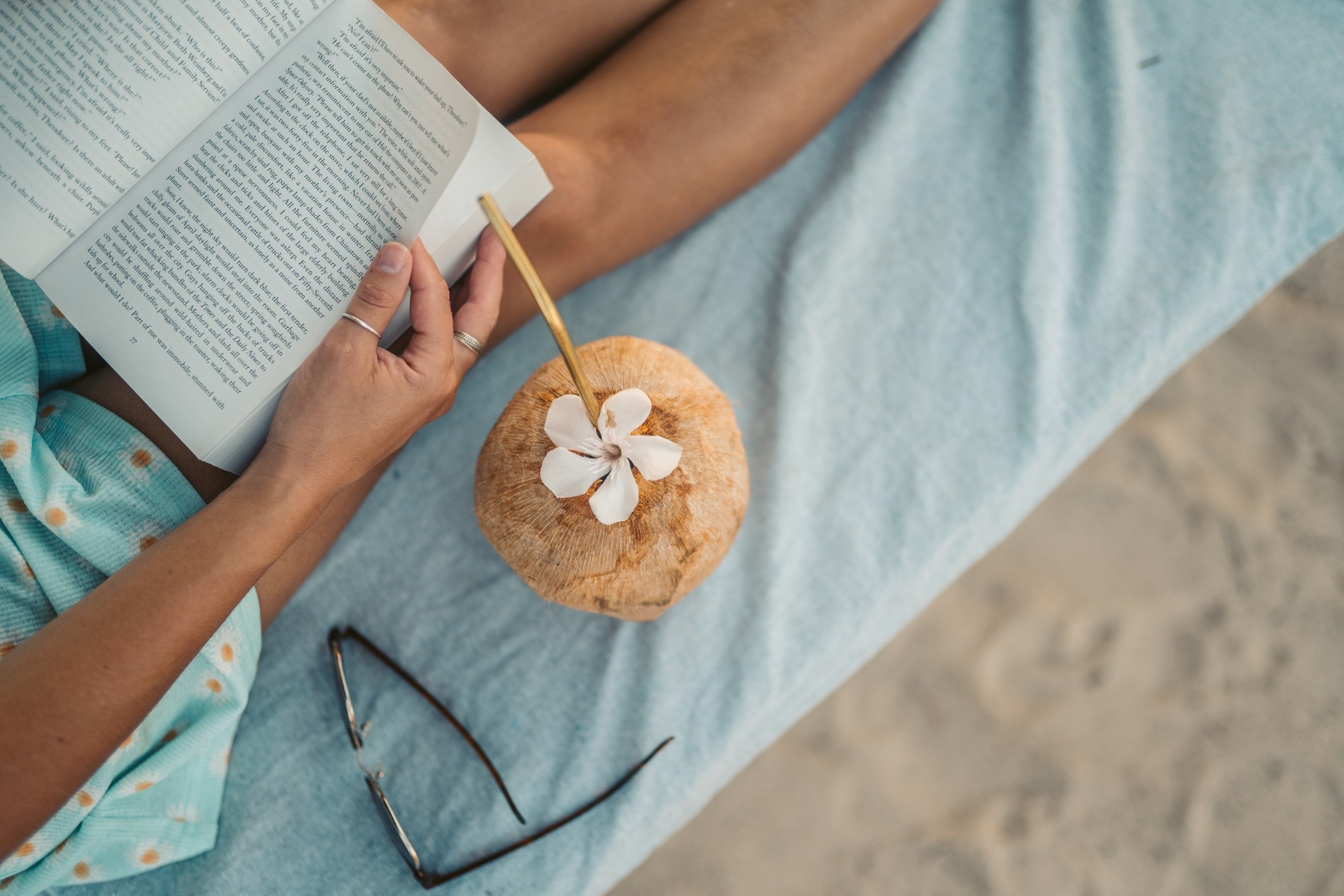 Woman reading book on beach with cookie nearby. June Medium Library Sandra Pawula