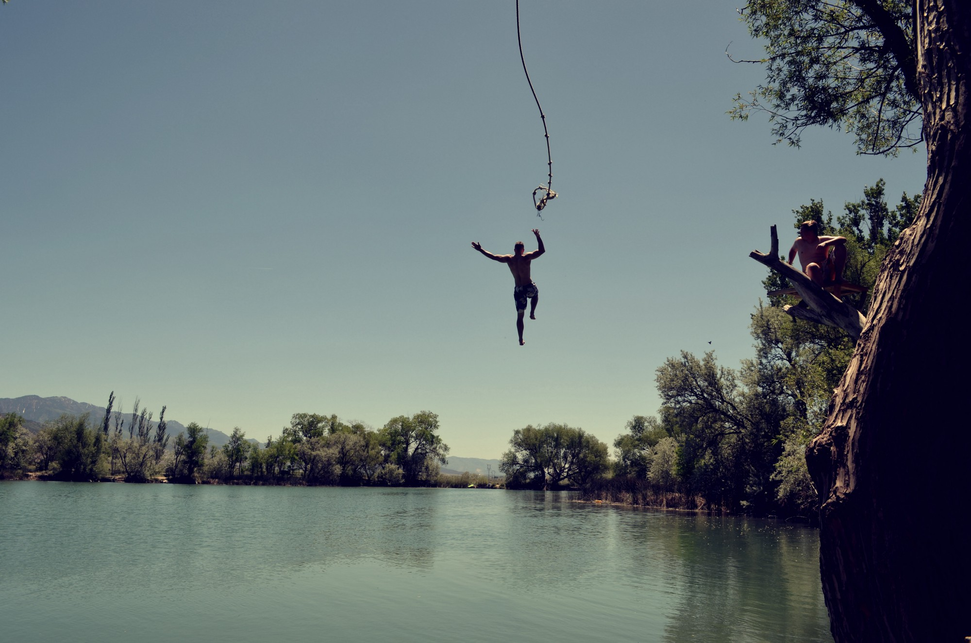 Photo of person jumping into a pool of water from a swing rope