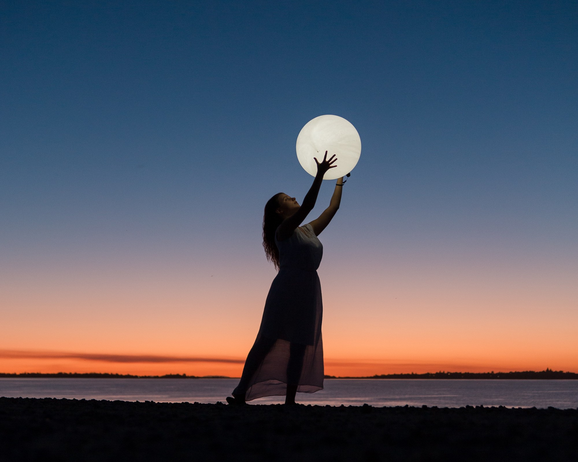 Woman holding the moon in front of a sunset