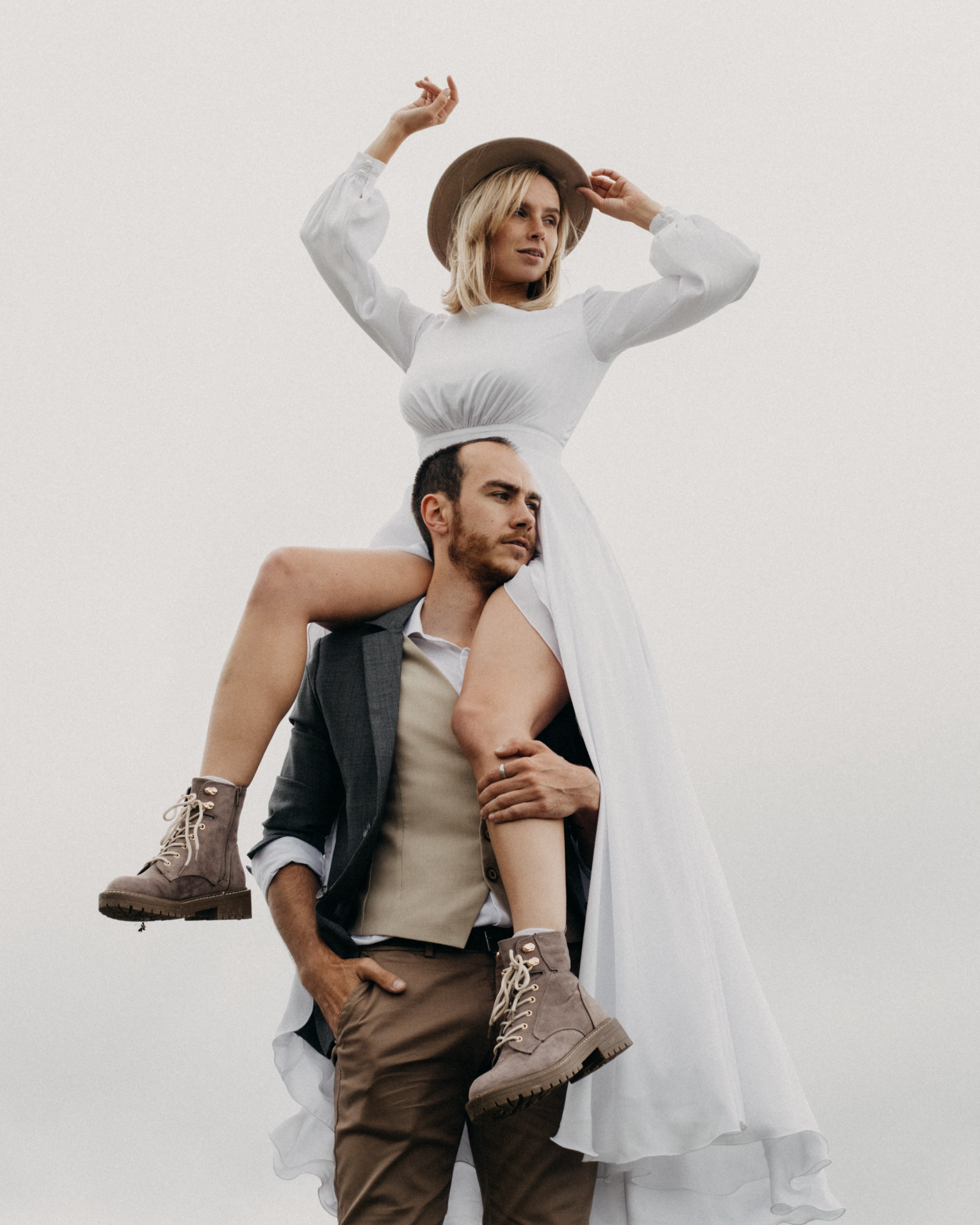 Woman in white dress, sitting on man's shoulders.