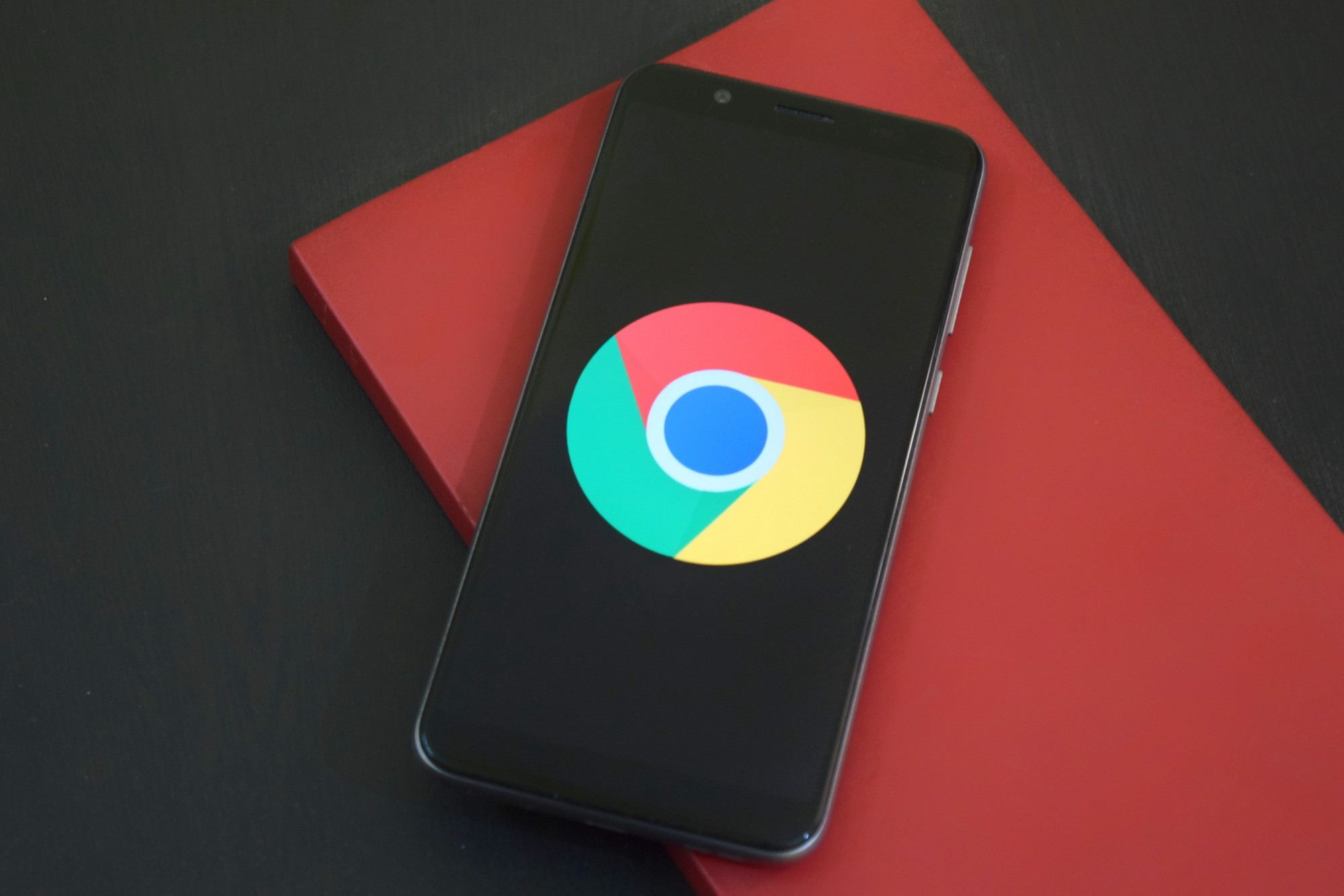 Black smartphone with Google Chrome logo sitting on red notepad