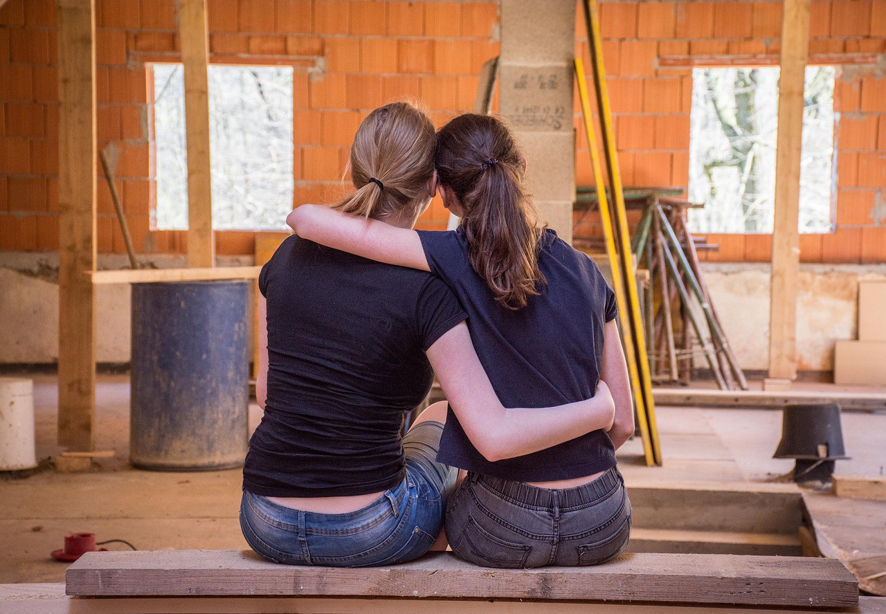 2 women remodeling a house are sitting together and embracing.