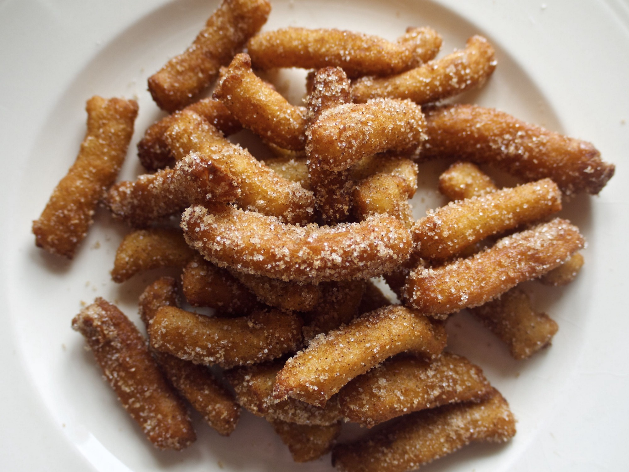 A photo of a plate piled high with homemade golden fried churros, tube-shaped dough that's dusted in sugar and cinnamon